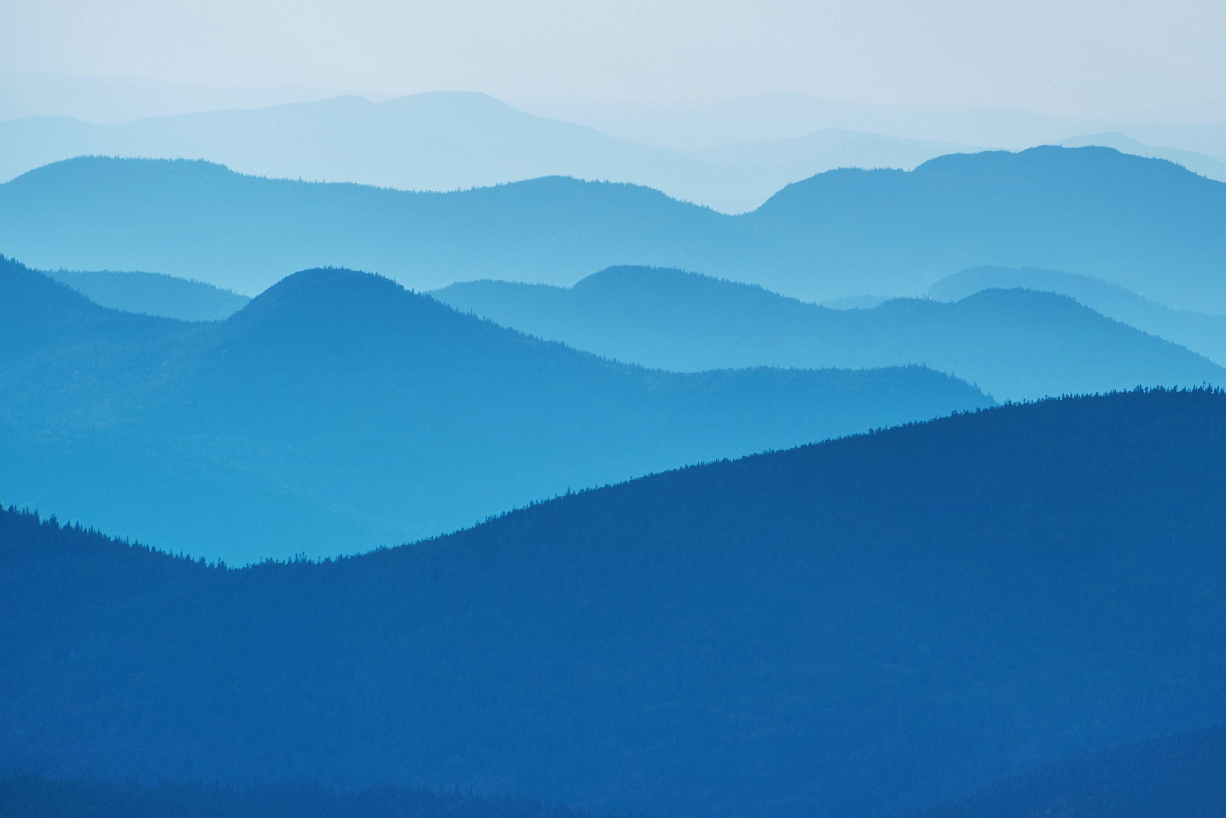 Blue-hued mountain ridges in a thick fog