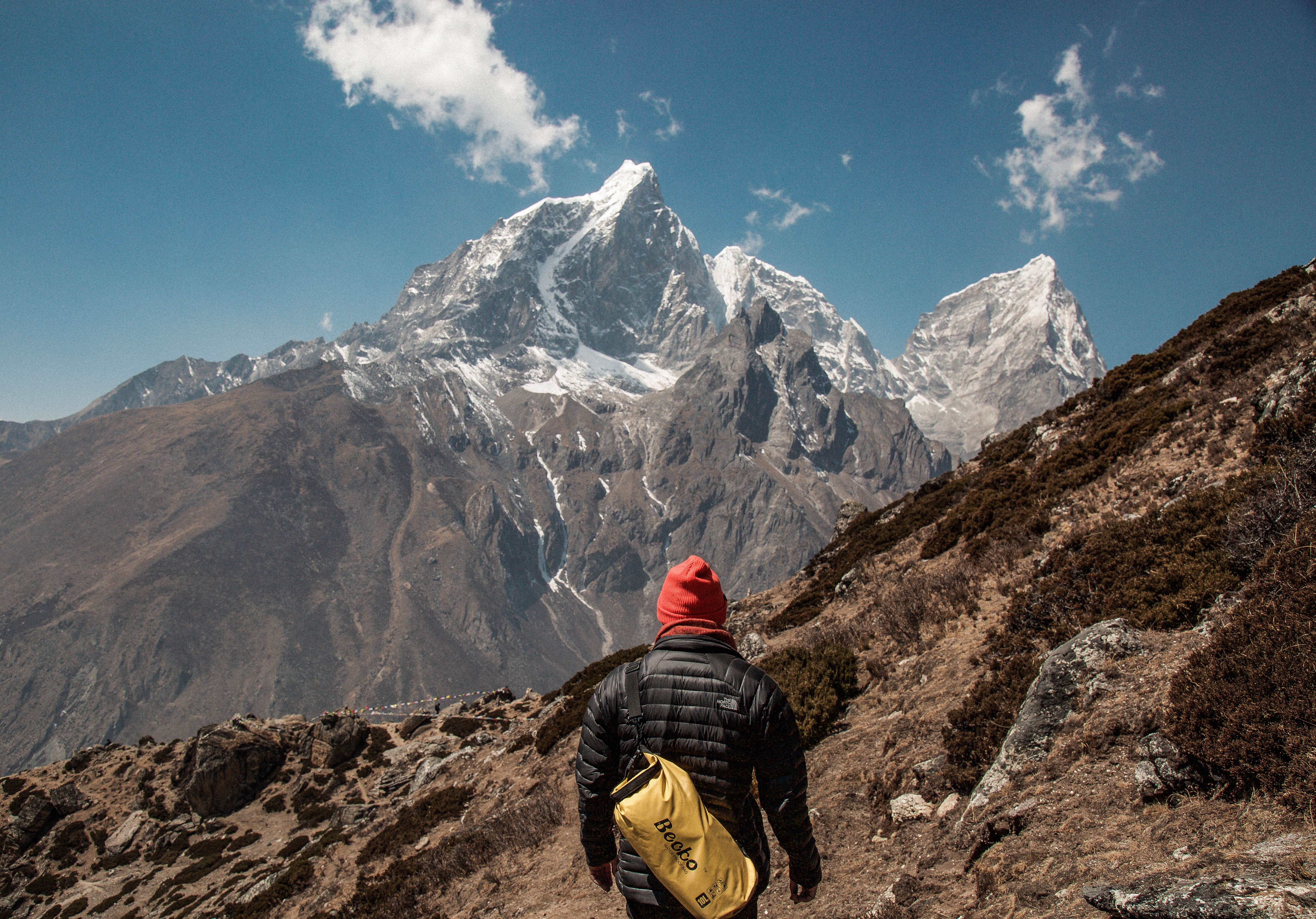 A hiker on a rocky slope looking away towards a tall snowy peak