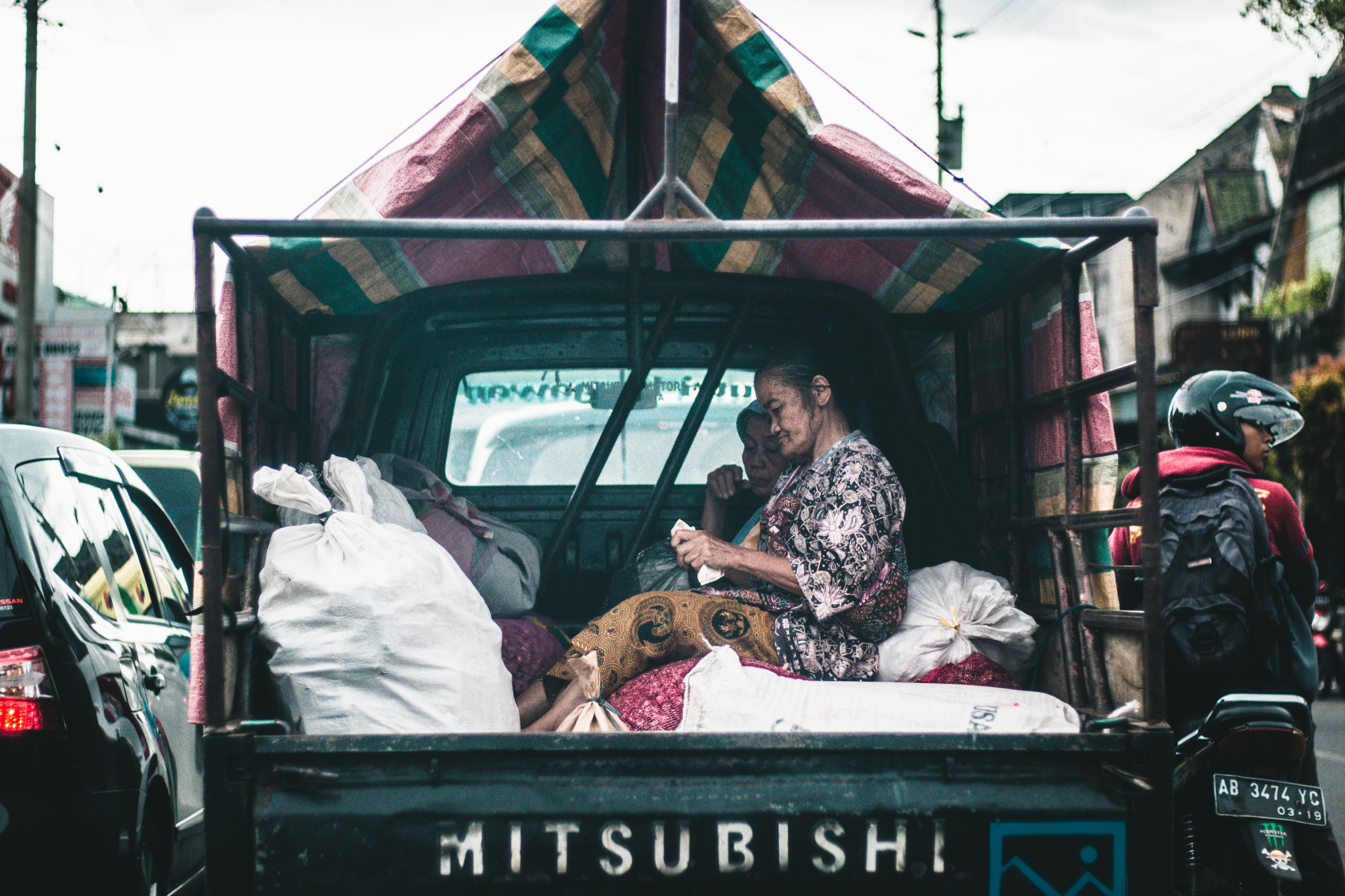 Two women sit on sacks in the back of a Mitsubishi truck