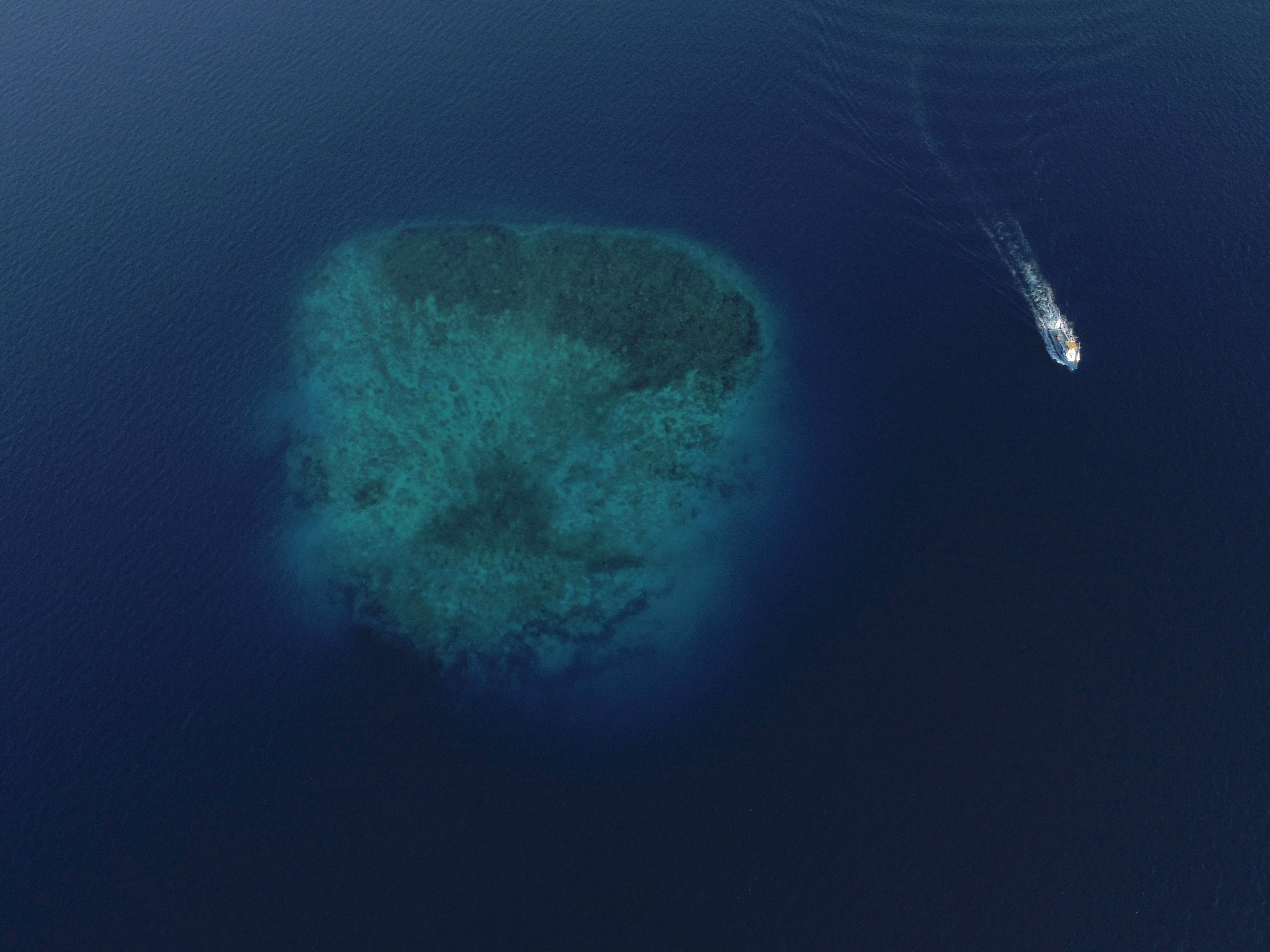 aerial photograph of boat near island under water