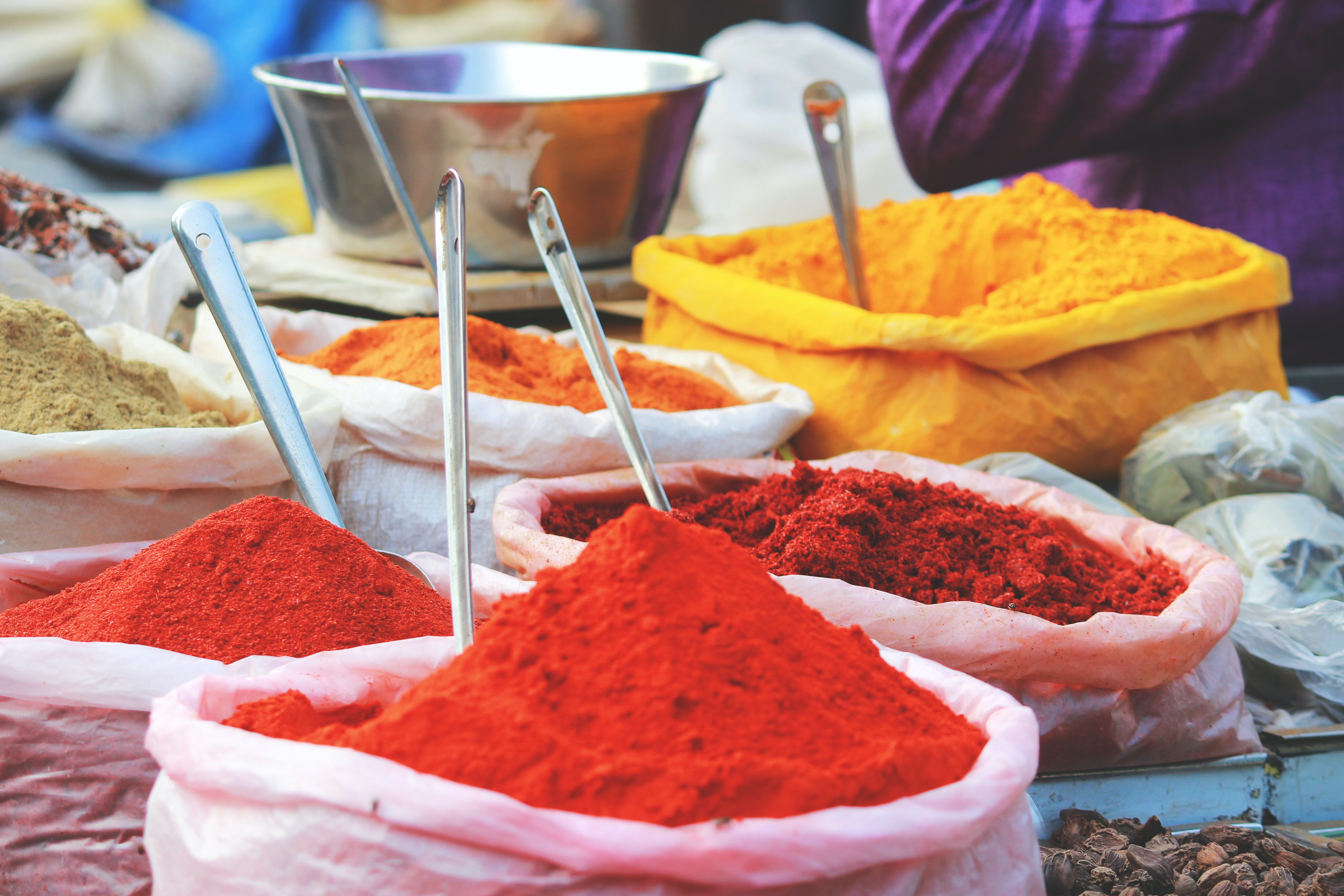 Red, tan, yellow, and orange spices in plastic bags with scooping spoons in a marketplace