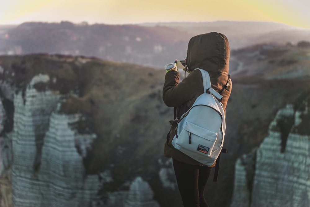 person standing near cliff holding camera