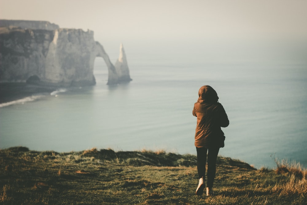 woman walking towards the edge of island facing the ocean during day