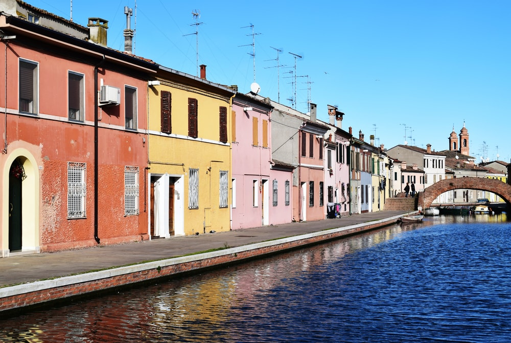 assorted-color painted houses beside body of water'