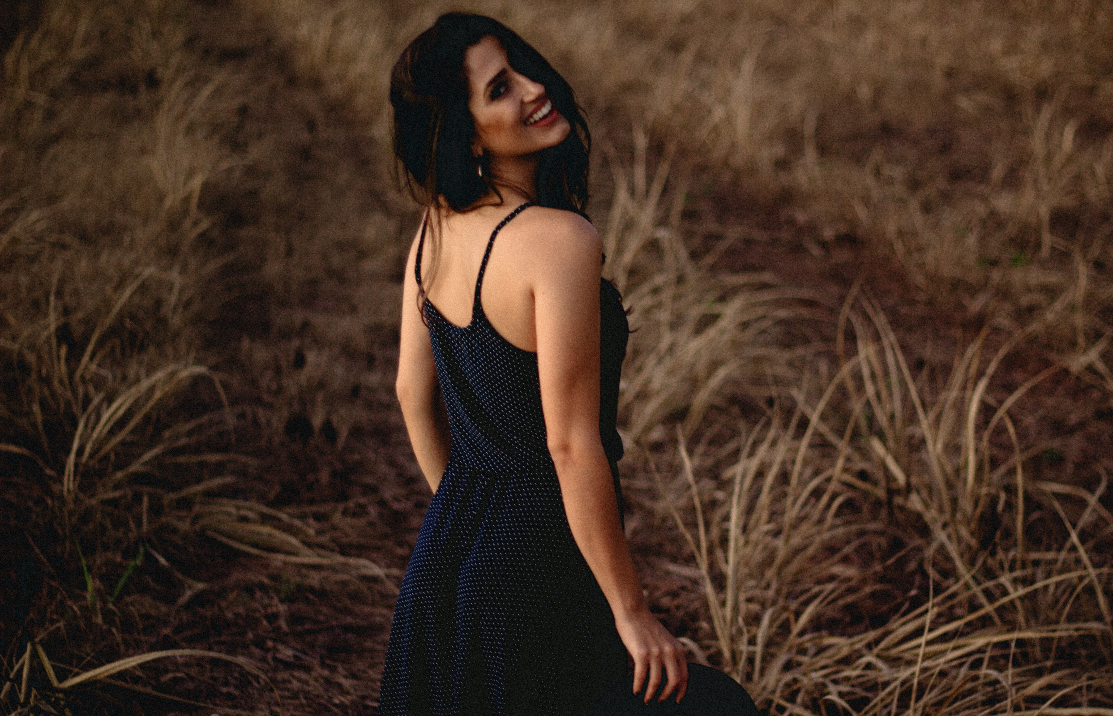 A woman in a black dress smiles over her shoulder in a field of brown grass