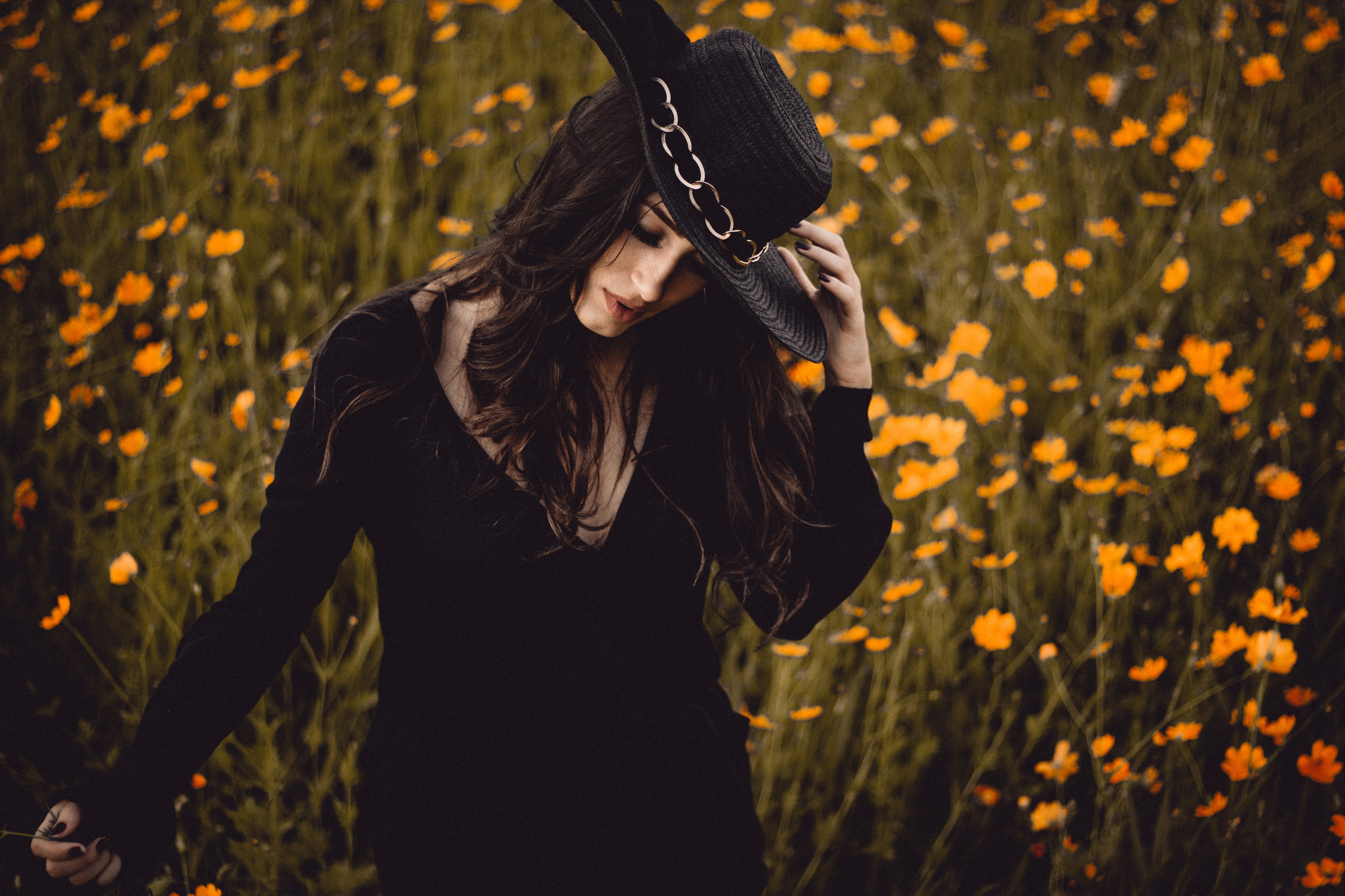 A dark-haired woman in a black hat and a black dress in a field of yellow flowers