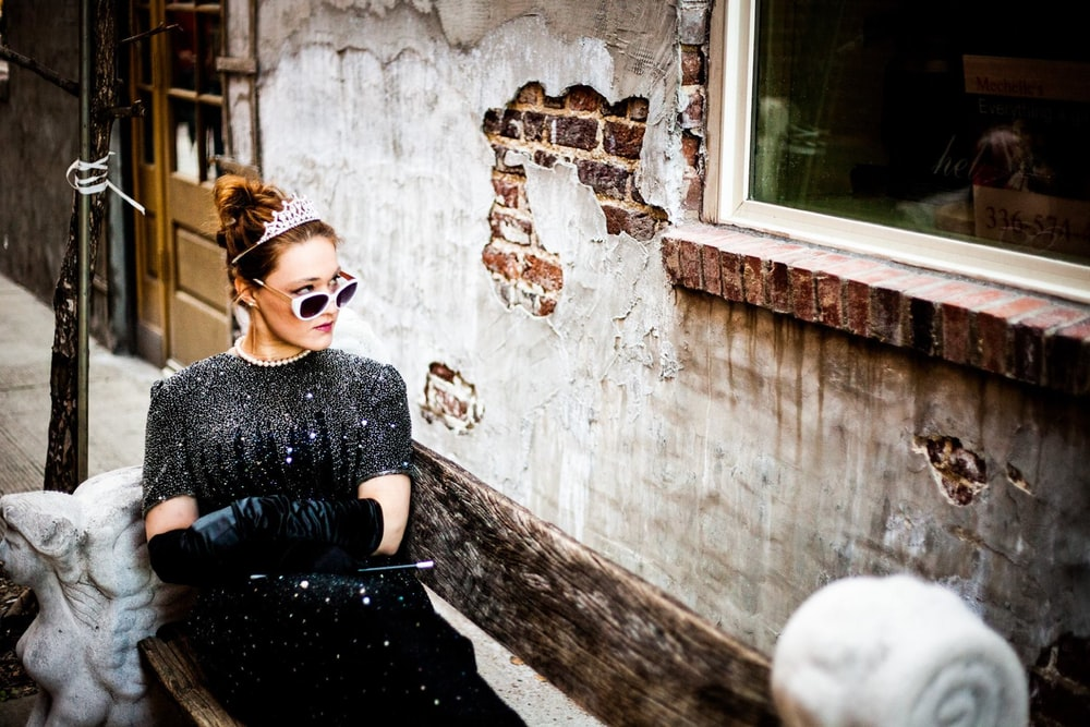 woman sit on bench facing on concrete wall