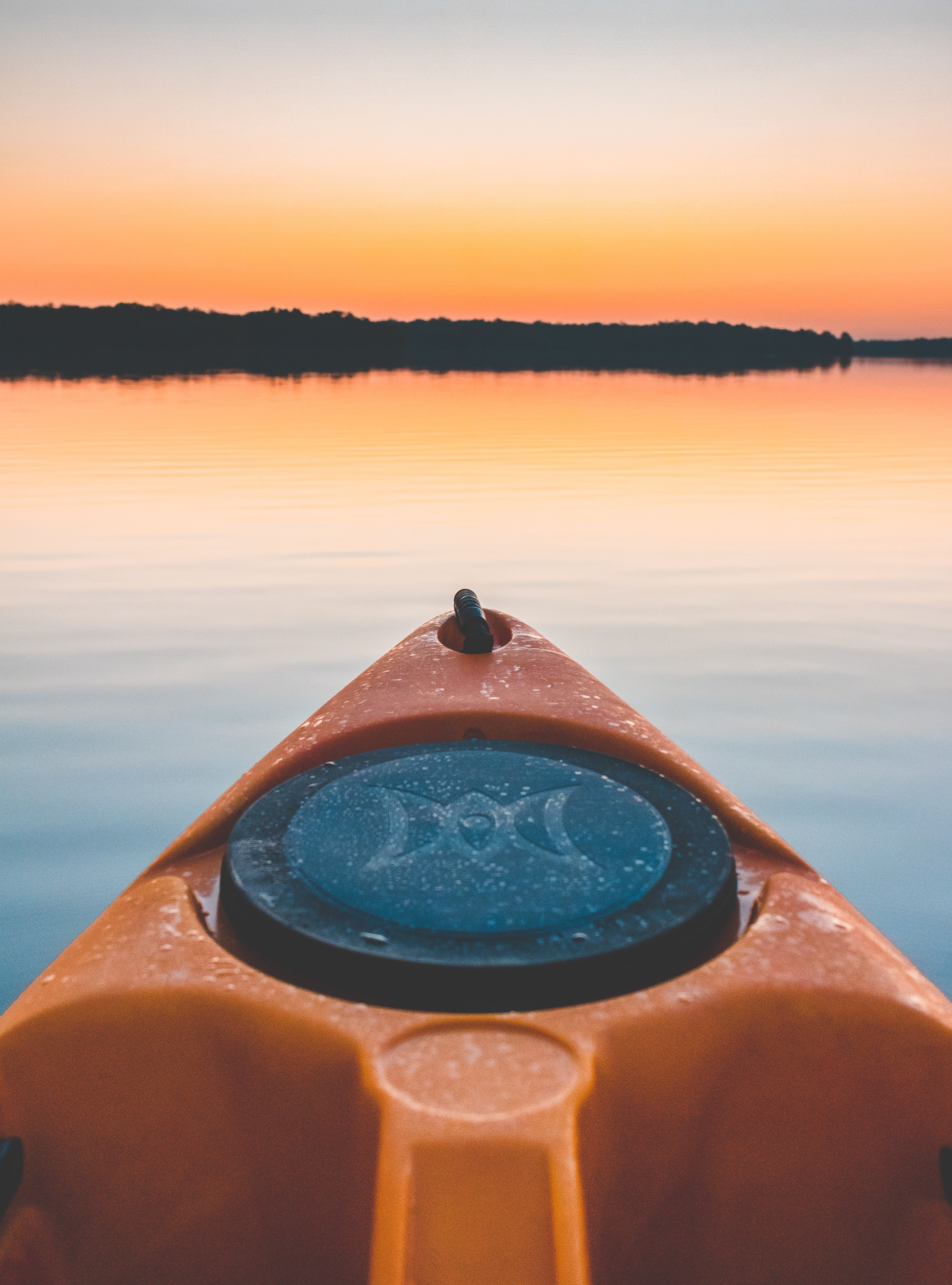 Front point of an orange and black kayak on calm water, trees in the distance, at sunset