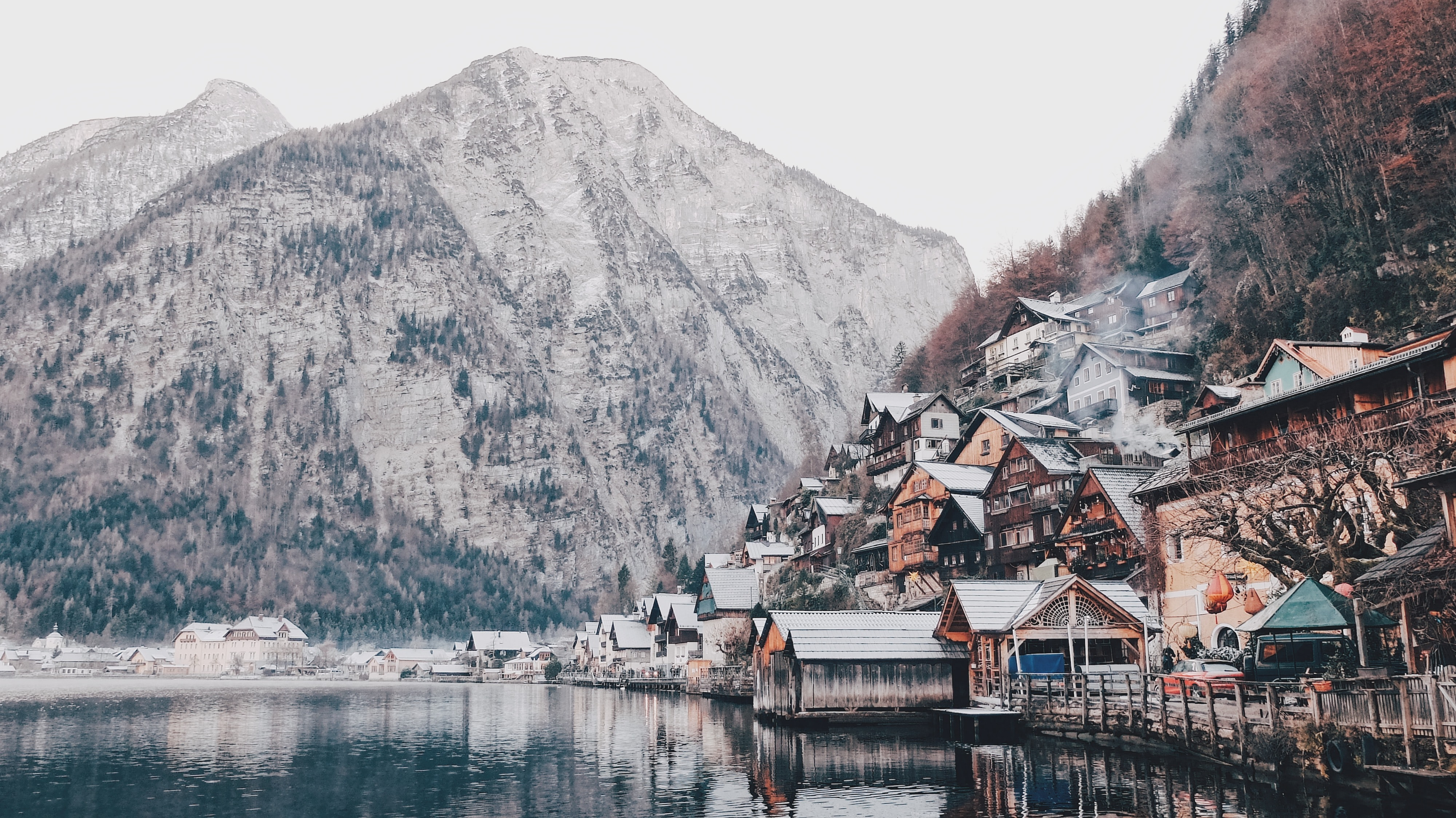 A picturesque village on the side of a wooded mountain by a lake