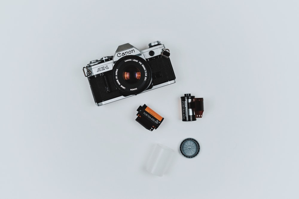 black Canon film camera with two films in flat lay photography