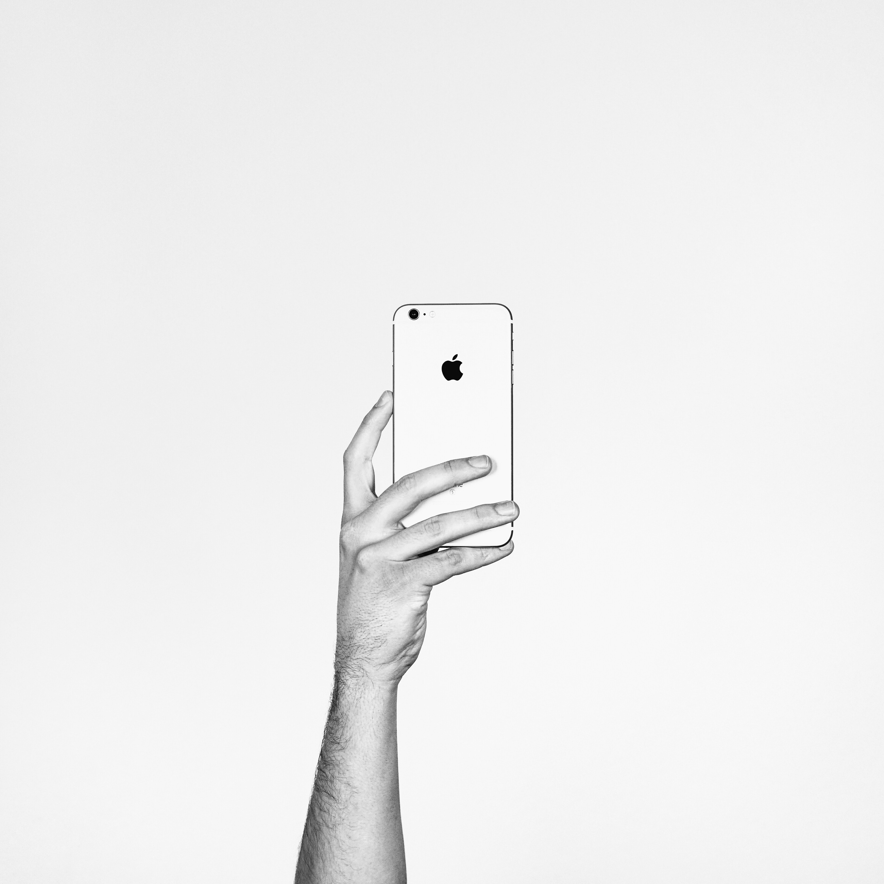 A person holding up an Apple phone.