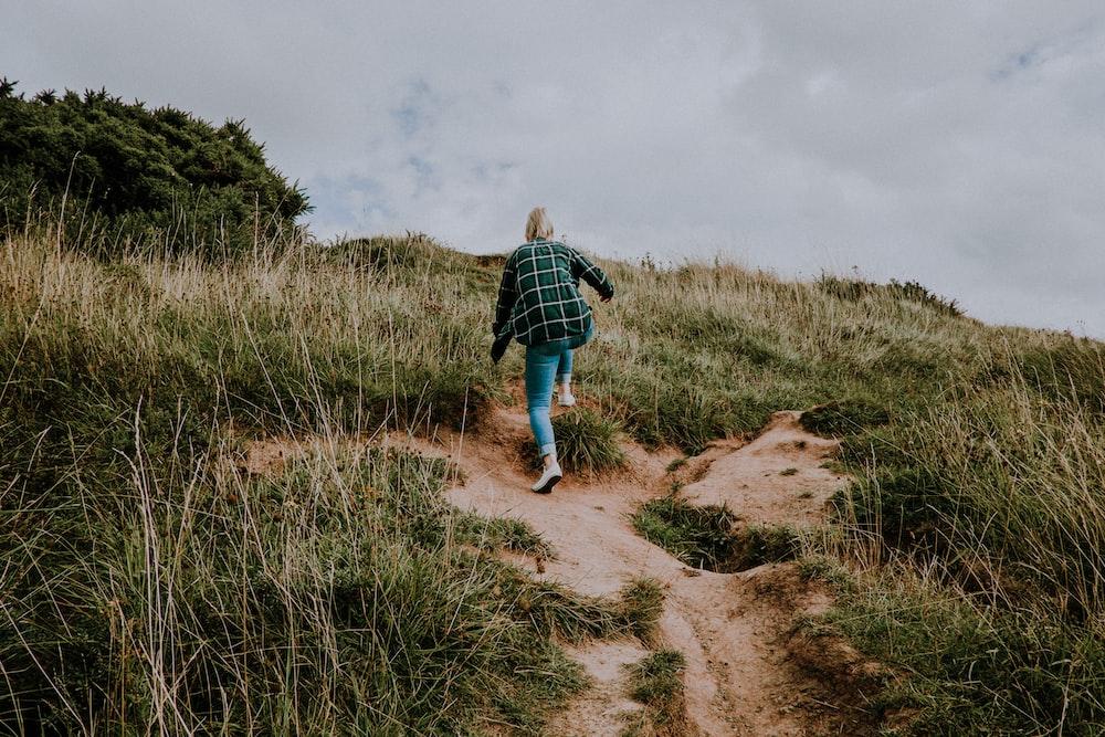 woman hiking on green mountain during daytime photo