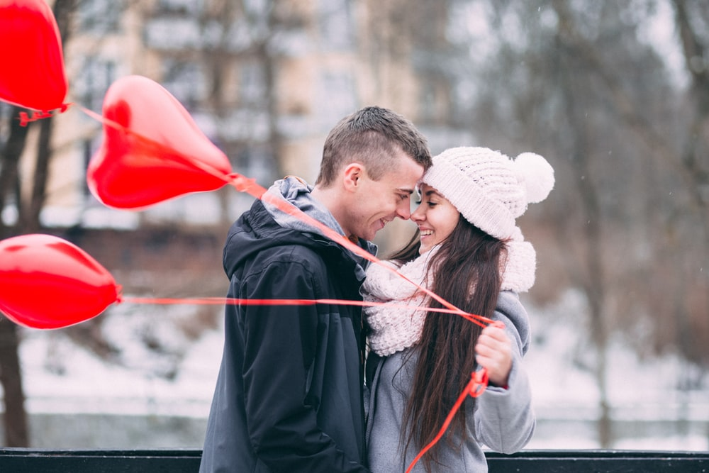 A man and woman smiling while touching face to face, as the girl holds red heart shaped balloons.