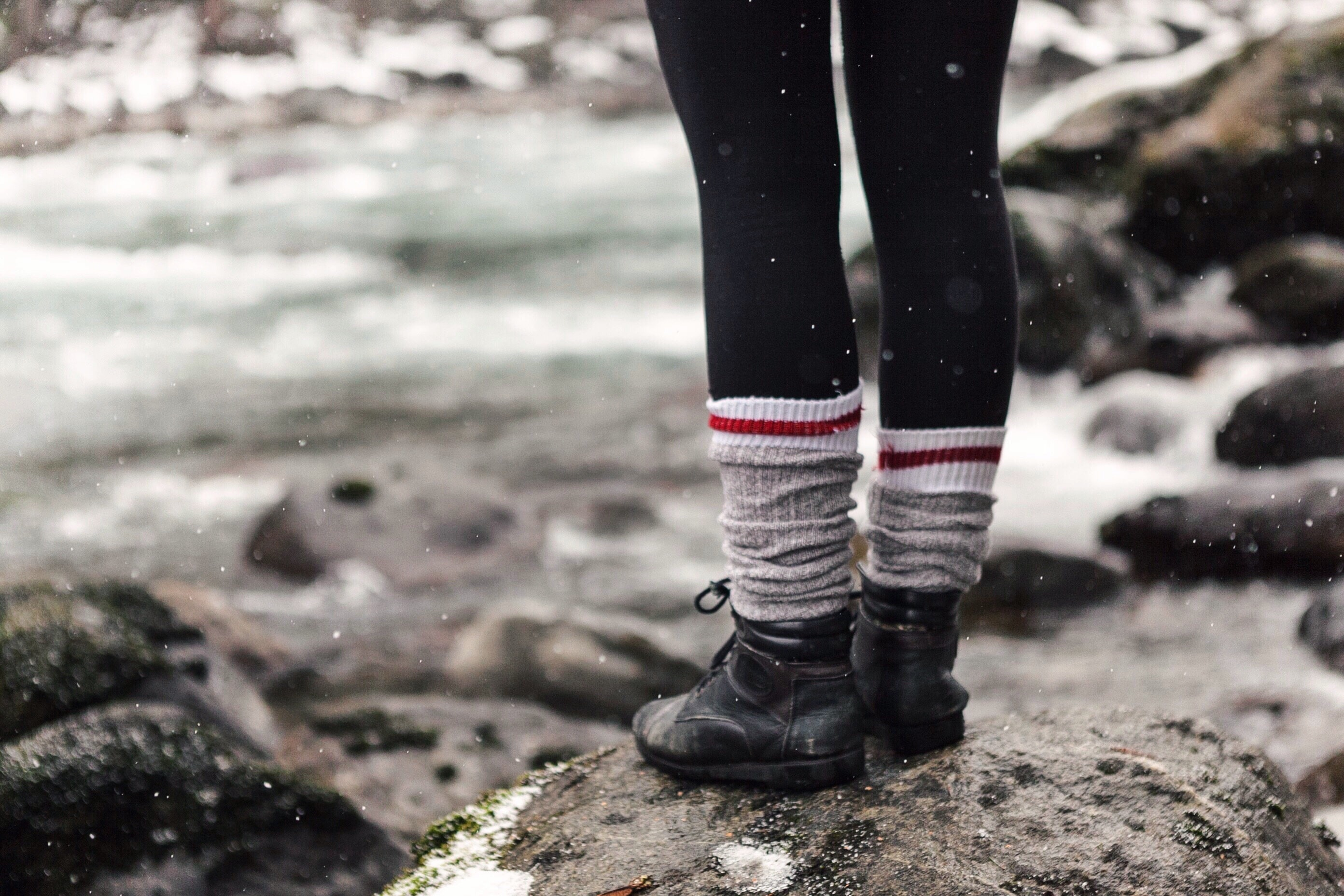 A person with leggings, black boots, and bunched socks stands on a rock during a light snow; only the person's legs are in frame