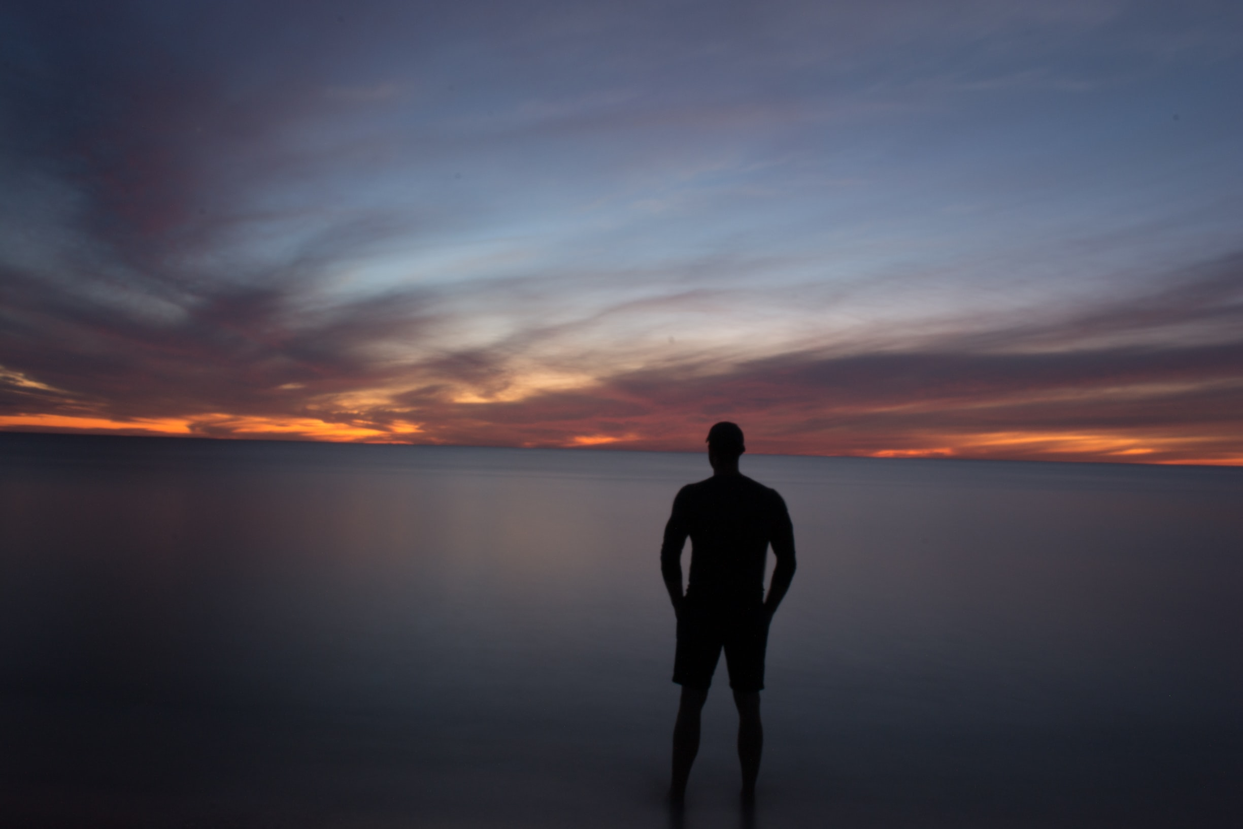 Silhouette of a man standing in calm waters, a cloudy blue and orange sky in the background