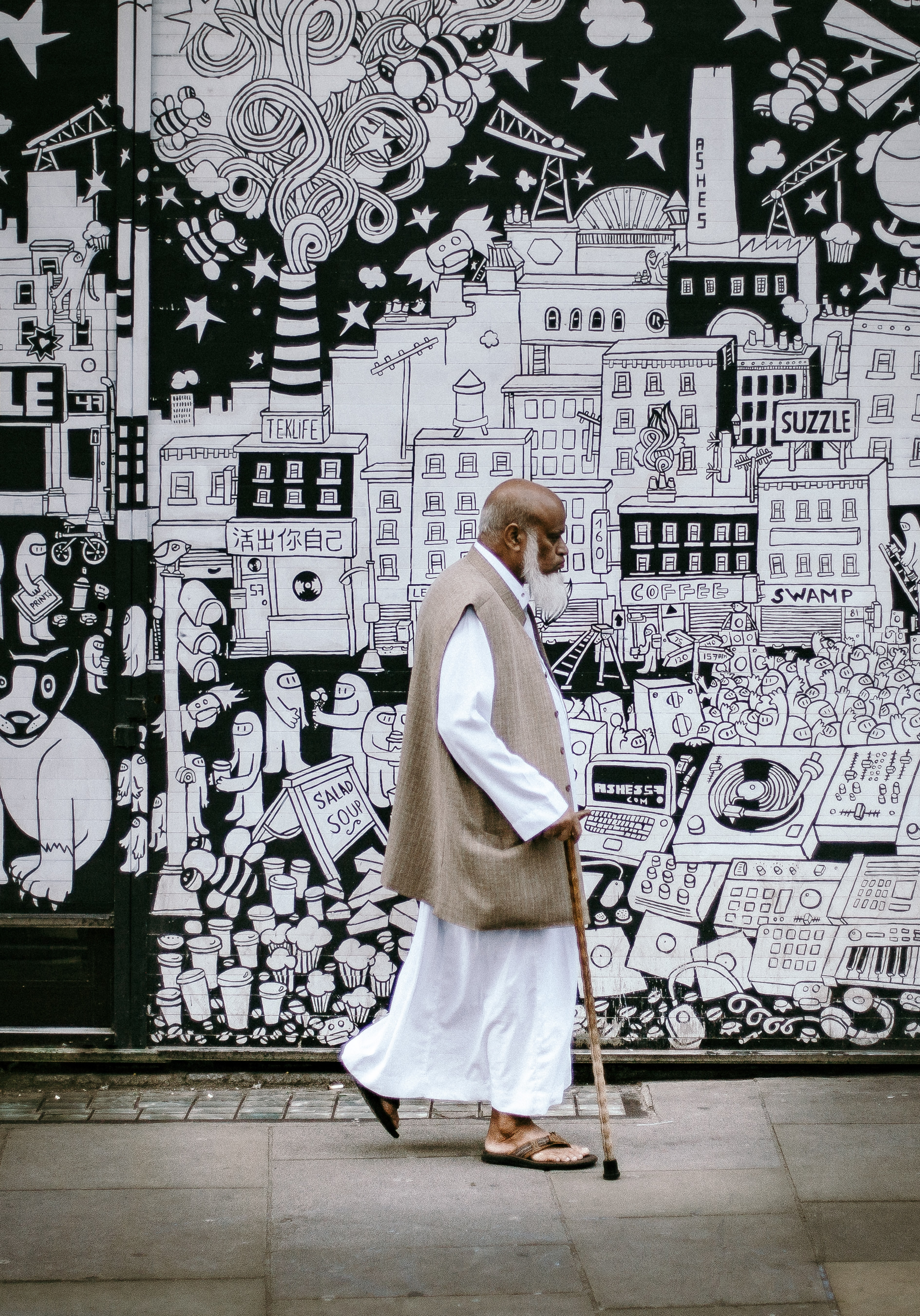 man wearing white sherwani robe beside graffiti