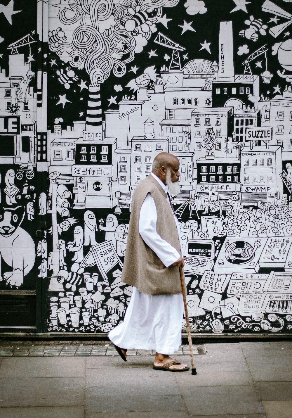 man wearing white sherwani robe beside graffiti