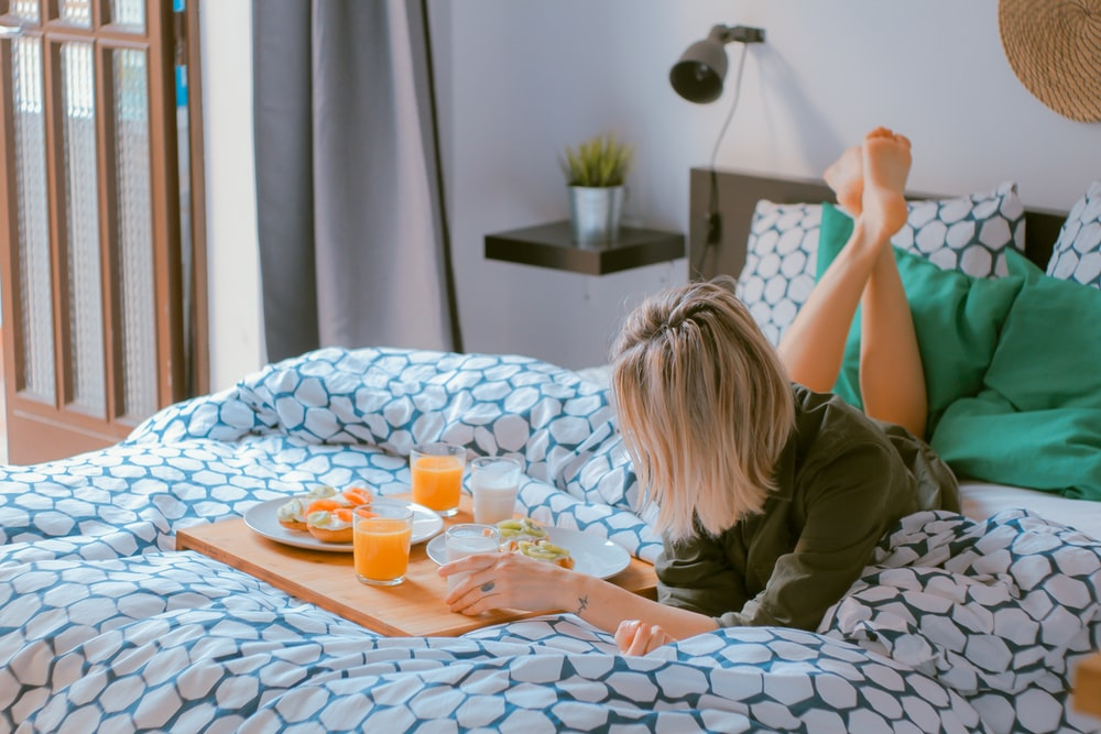 A woman laying on her bed, eating breakfast on a blue and white bedspread in her bedroom in her apartment in Barcelona