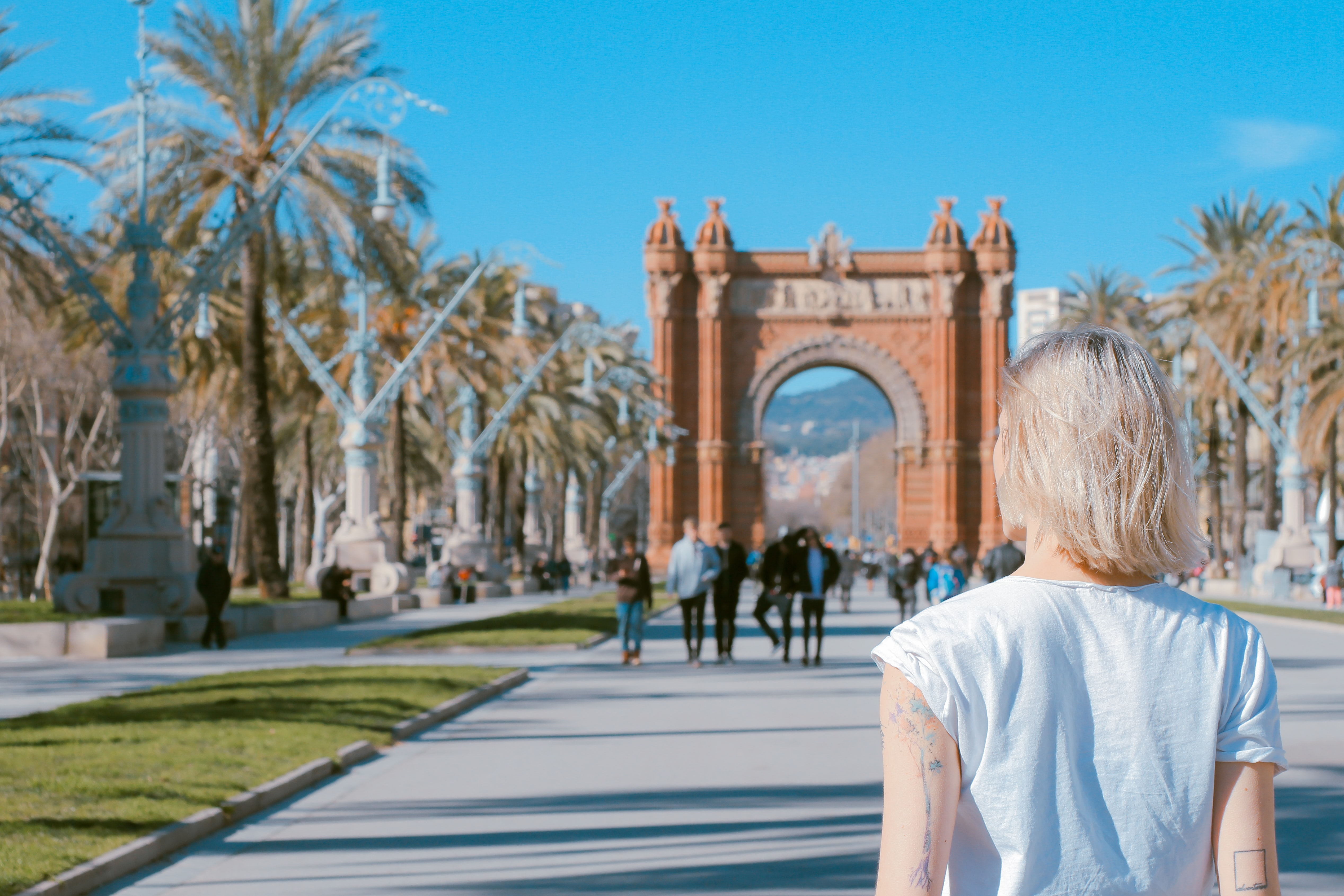 Rear view of a blonde woman walking on a road under a triumphal arch in Barcelona