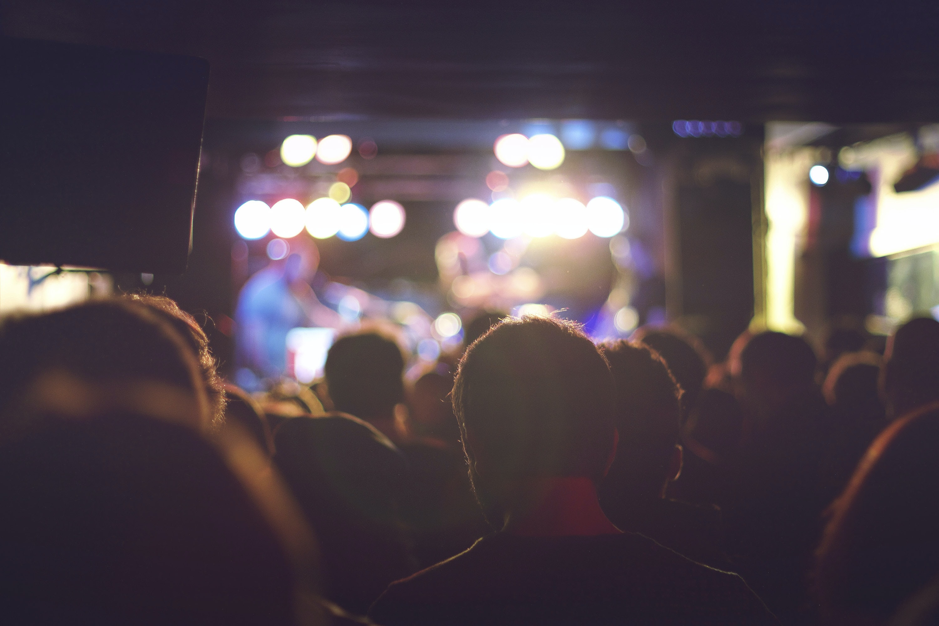 View from a crowd in a concert showing light on the stage in Café La Palma
