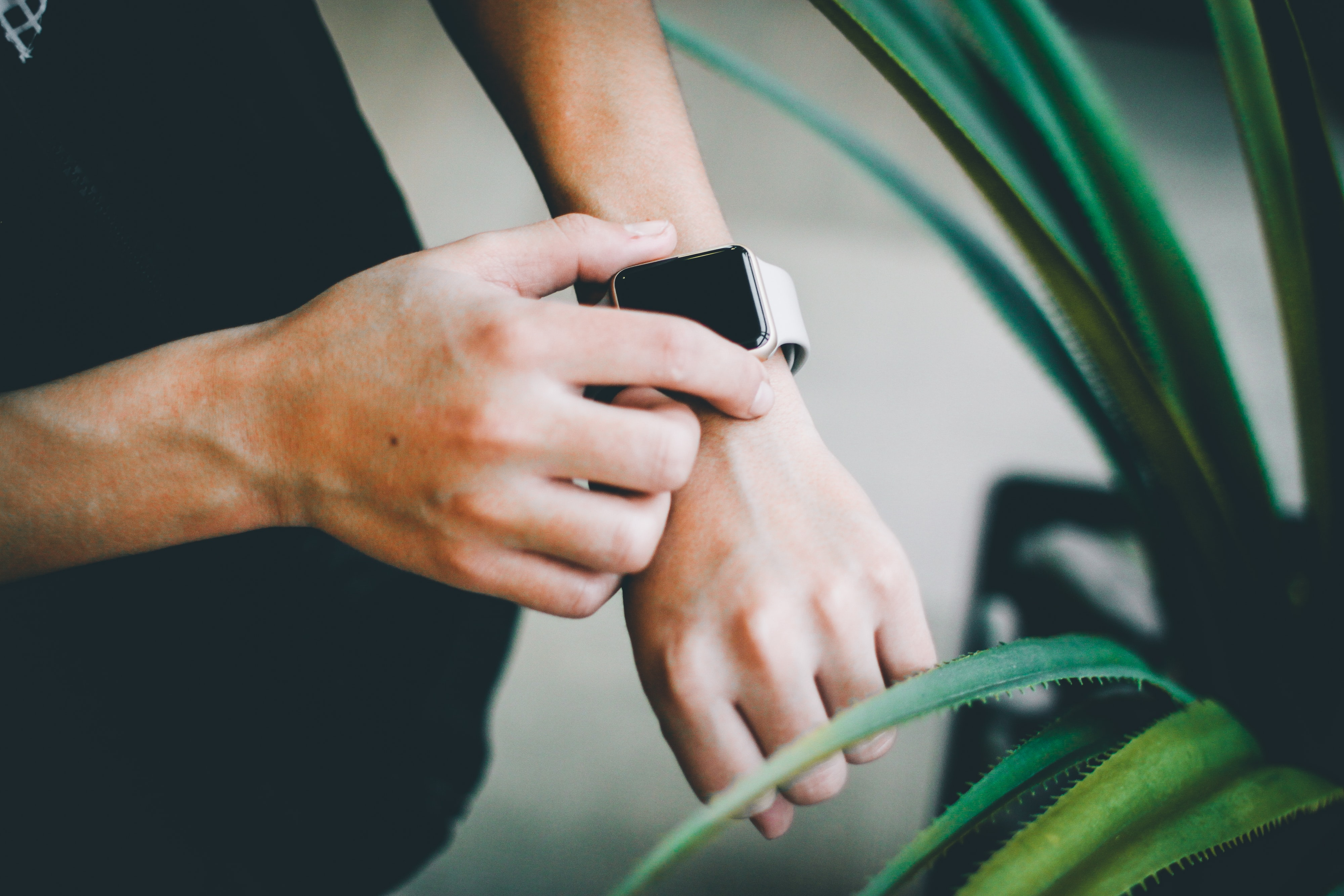 person about to use silver Apple Watch in grey Sports Band