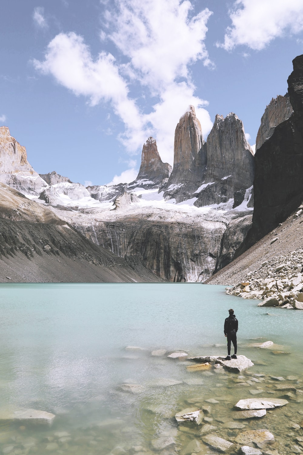 man standing above rock beside body of water under cloudy skies