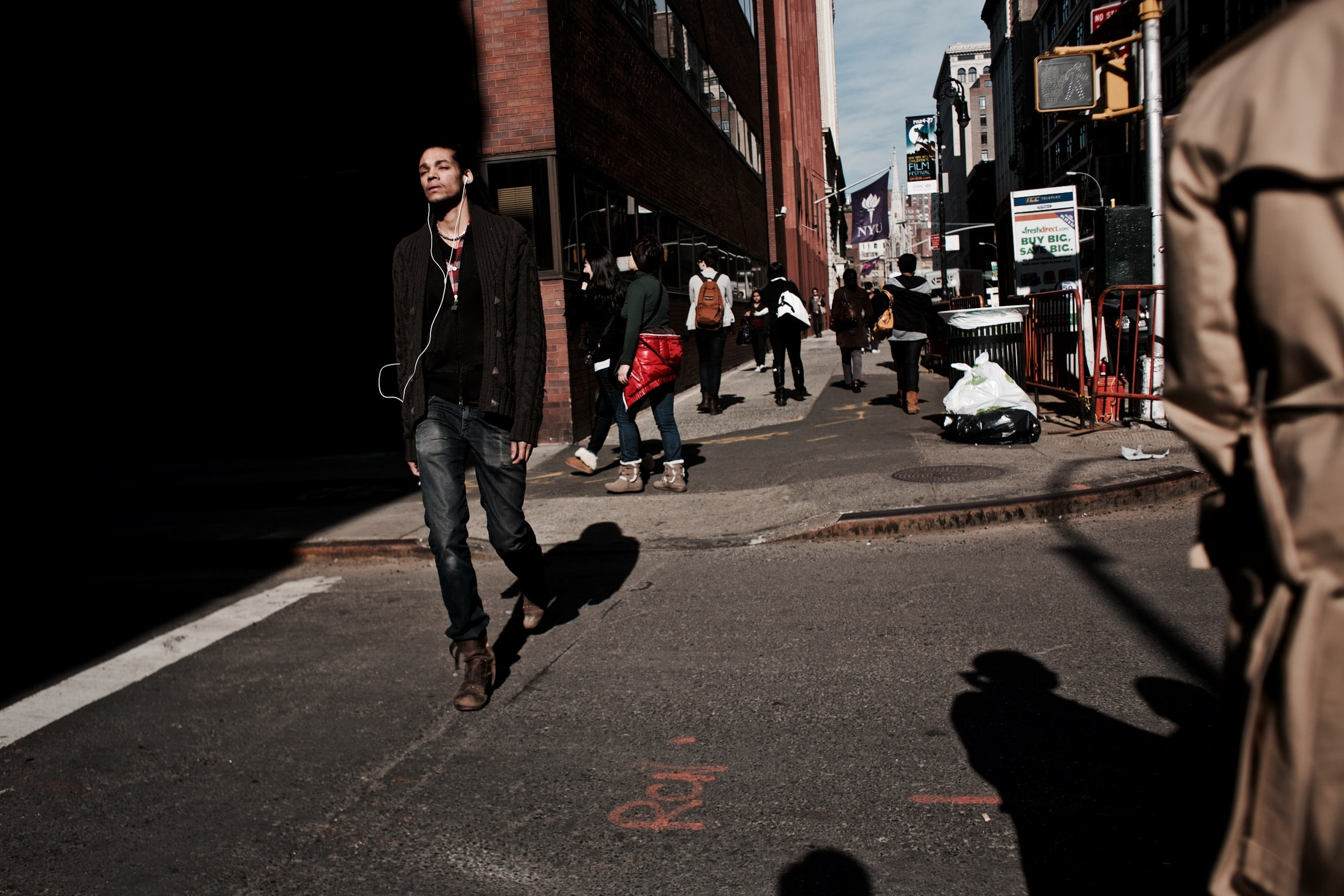 A young man walking down the street listening to music on white earphones