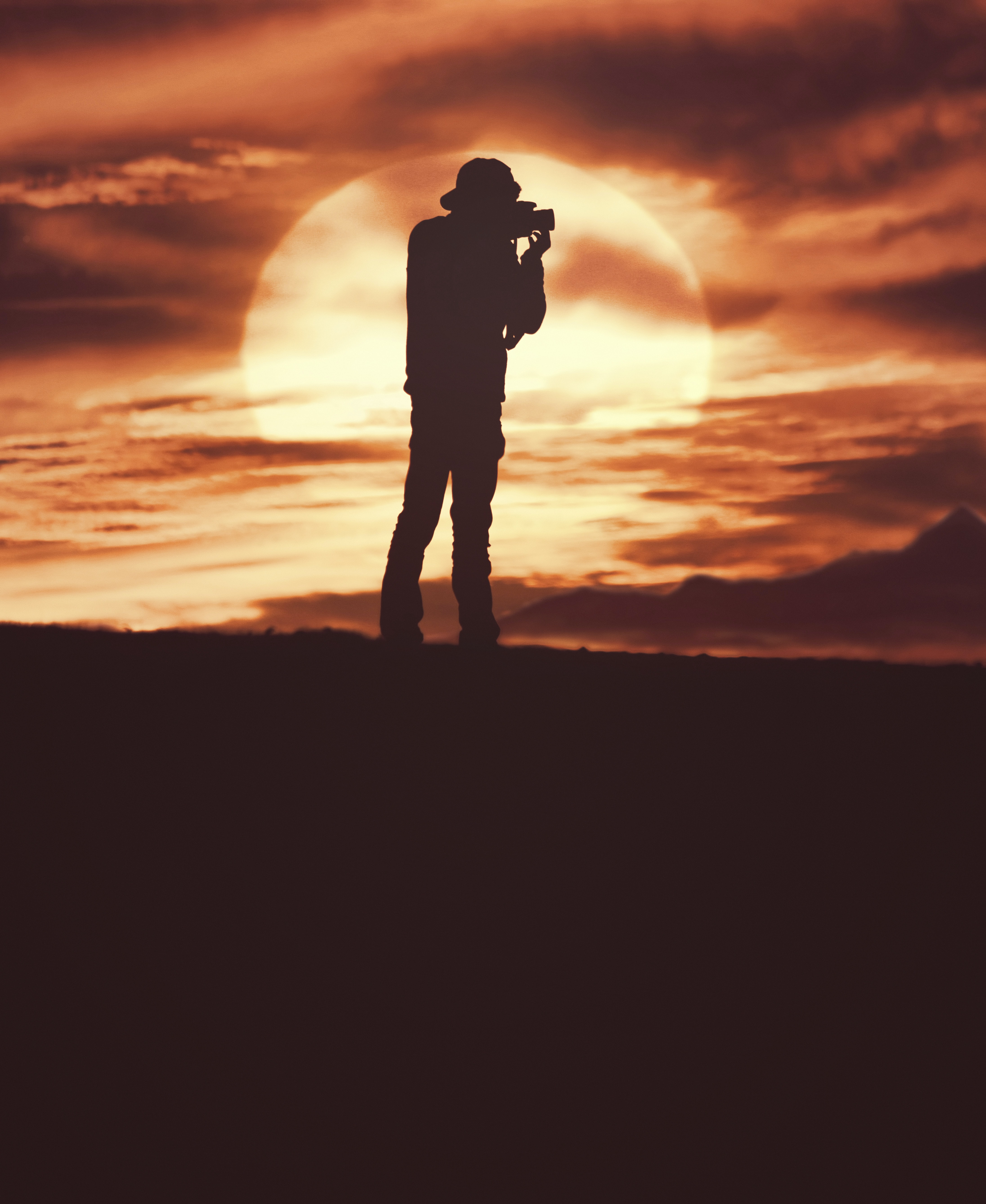 A silhouette of a man in a hat holding a camera in front of a cloudy orange sunset sky, Asilah, Morocco