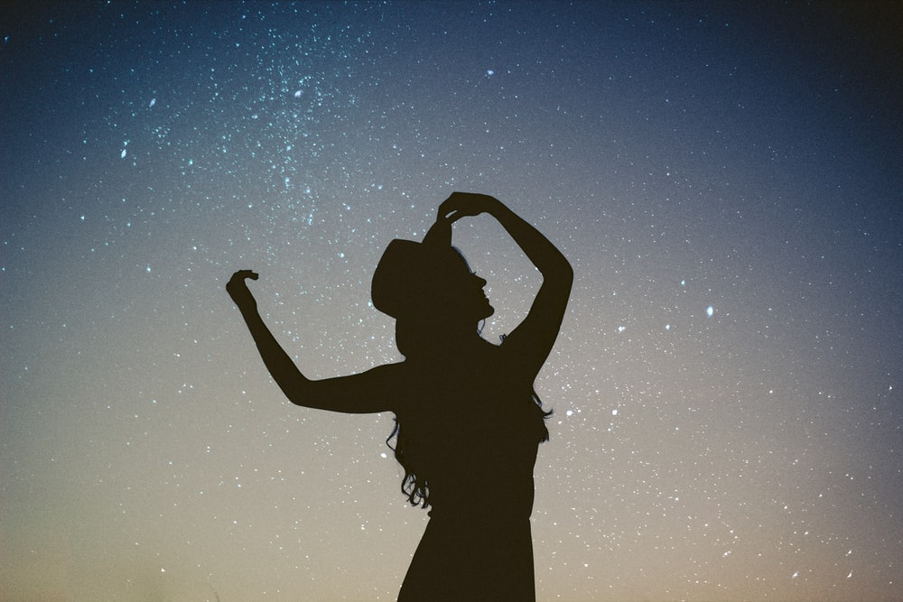 silhouette of woman holding hat in blue and gray nebula
