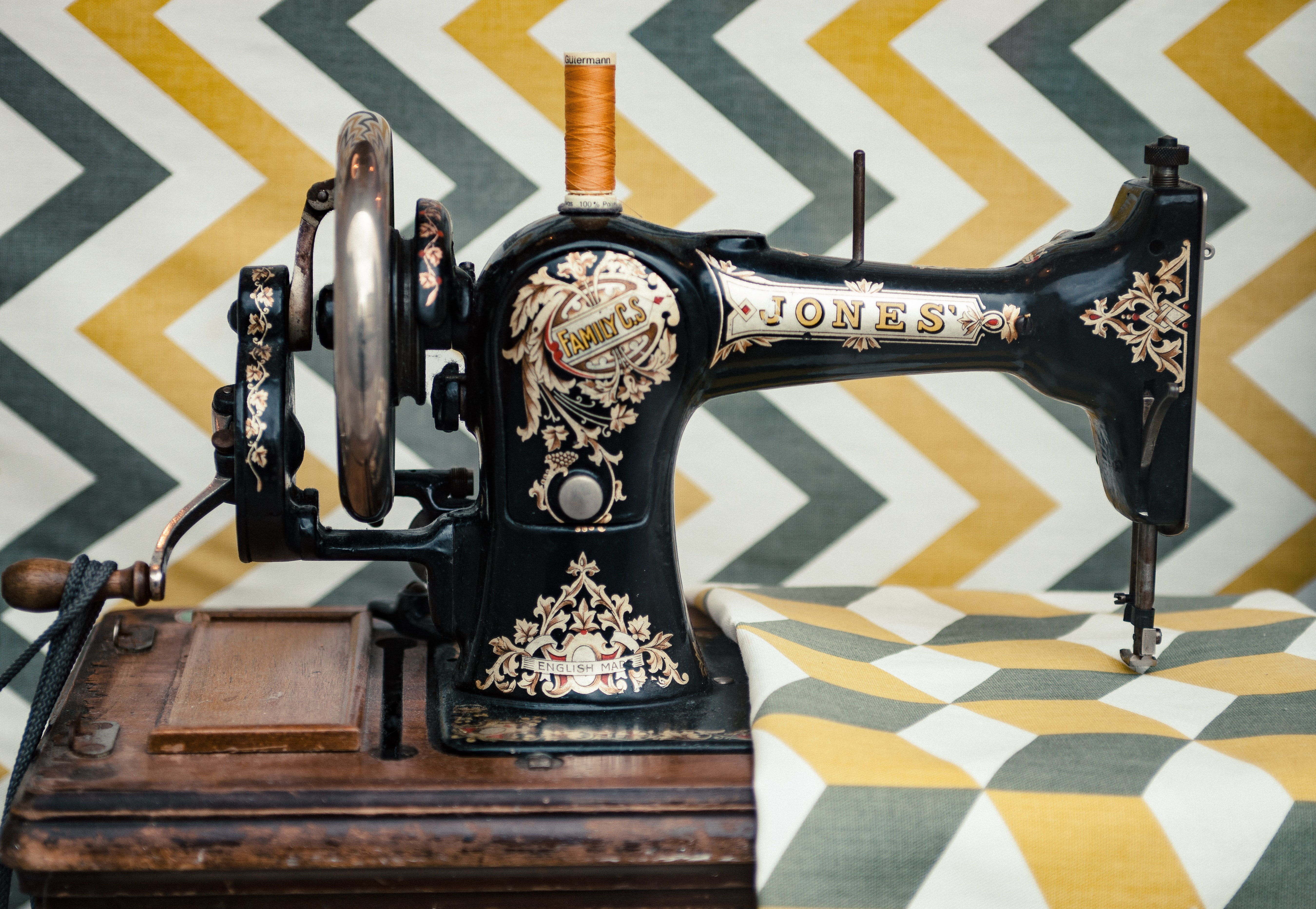 The side view of an old vintage sewing machine sewing on a patterned fabric in cambridge.