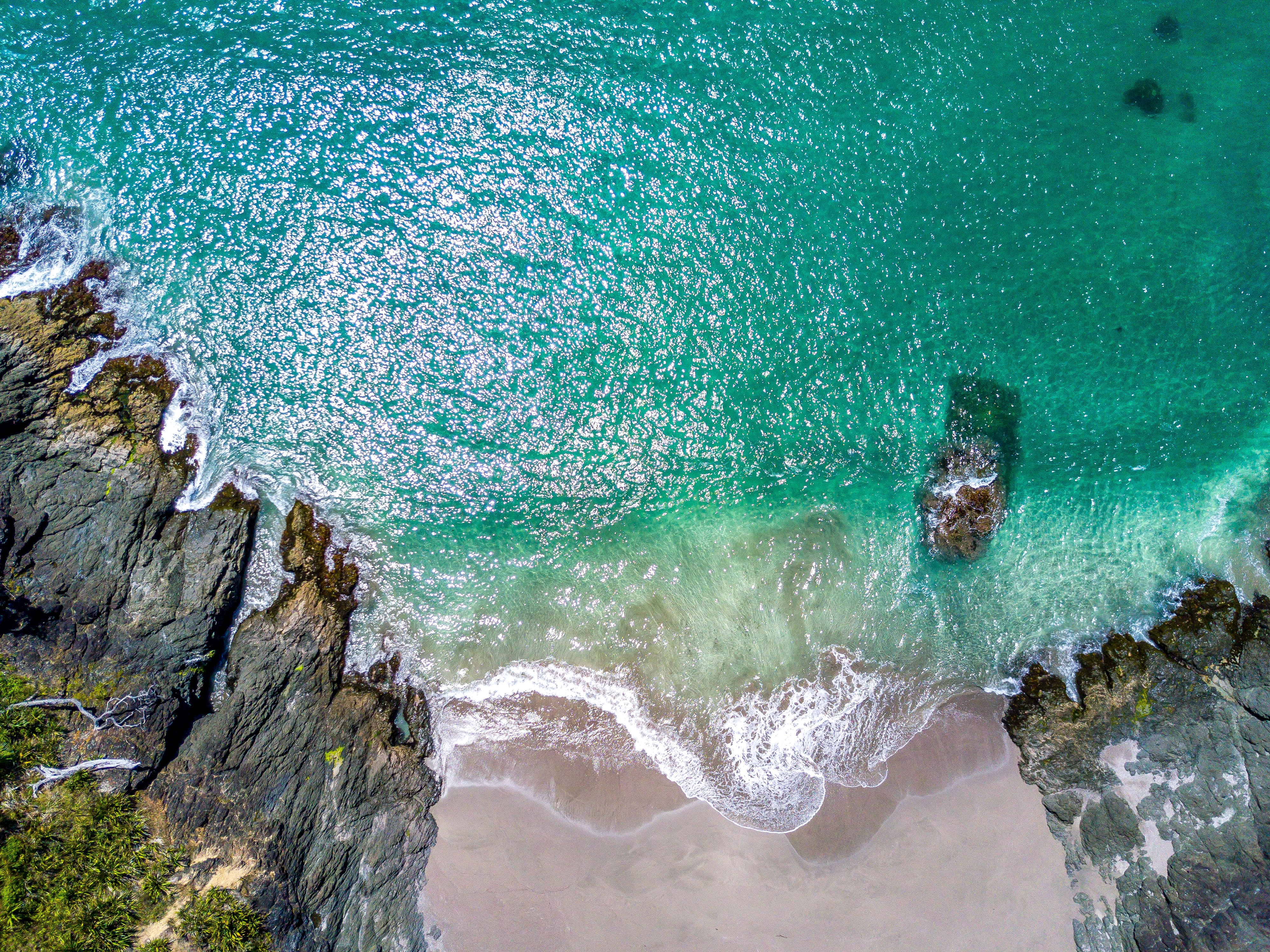 Drone view of an ocean washing on sand shore between rocks