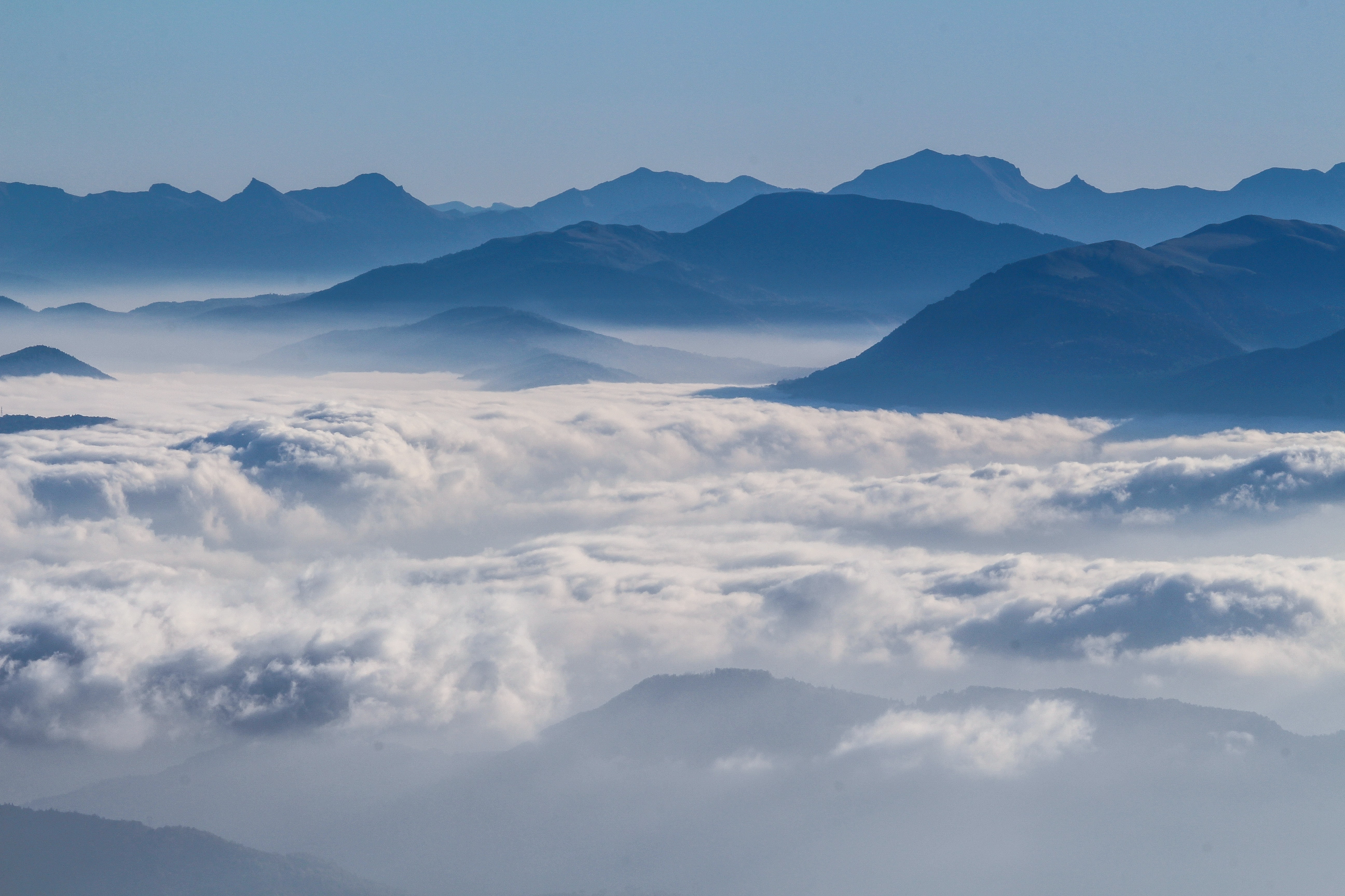 Silhouettes of mountains rising up above a thick cover of clouds