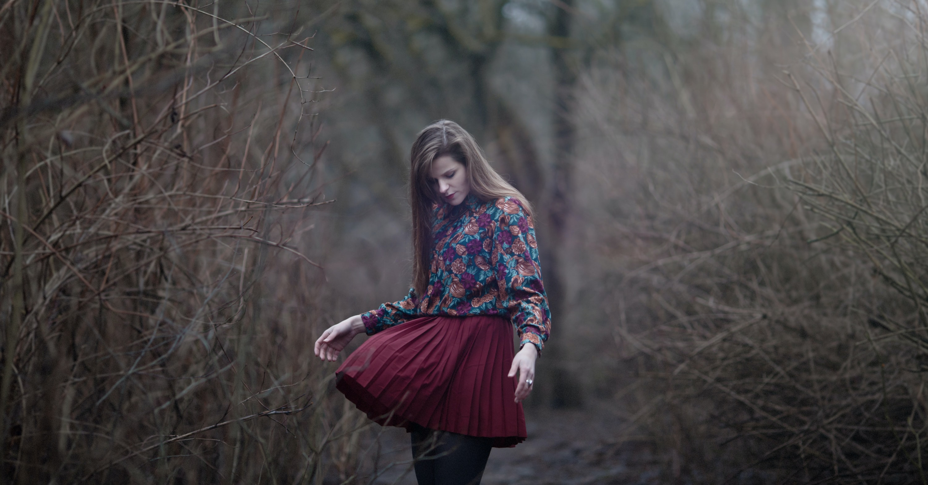A woman looks down at her billowing skirt on a path among dead trees in Vilnius