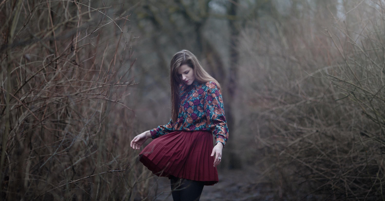 woman standing in between grass fields