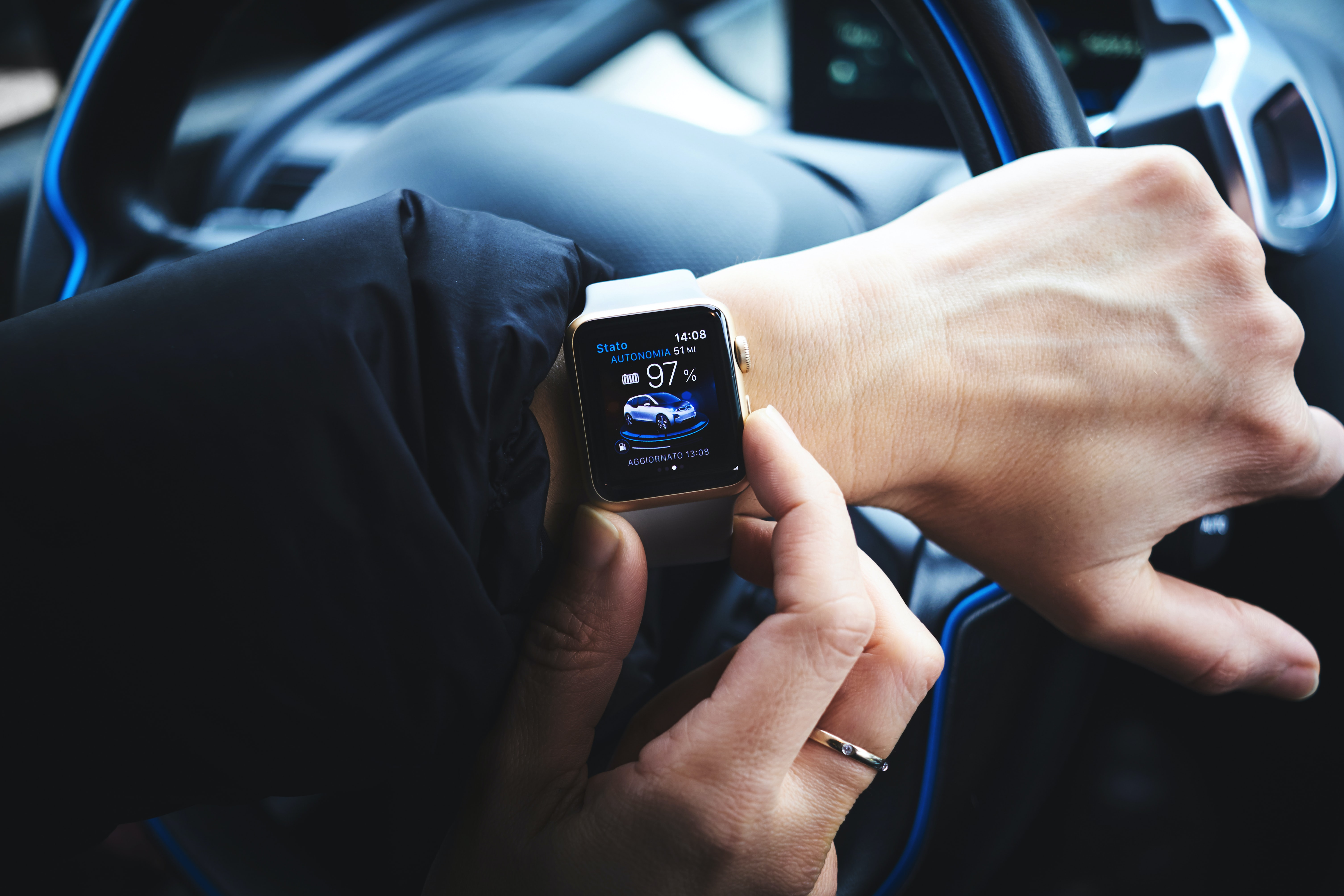 A person using an Apple Watch while driving a car