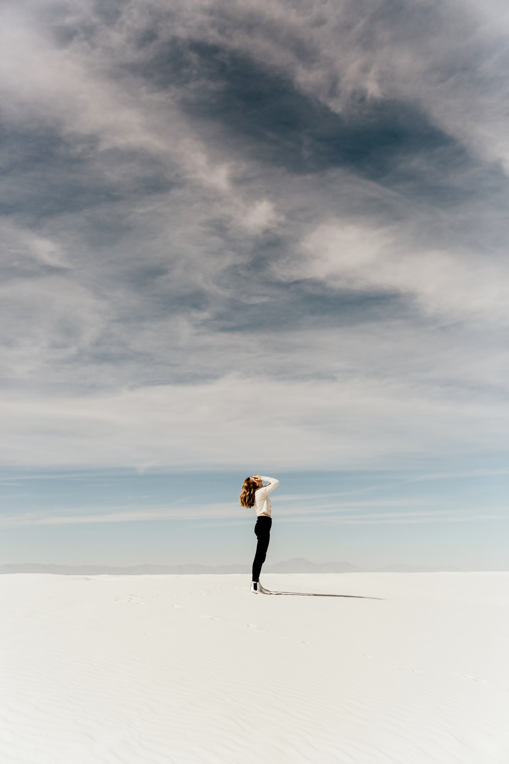 woman looking up to the sky while standing on white sand