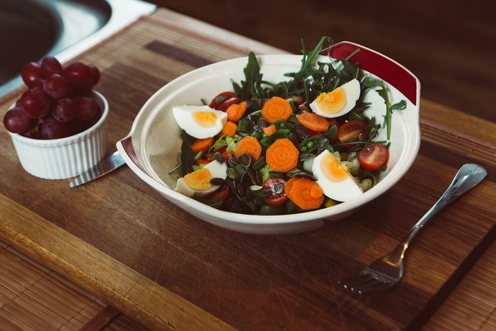 bowl of salad with slide of cooked egg with grapes on the side