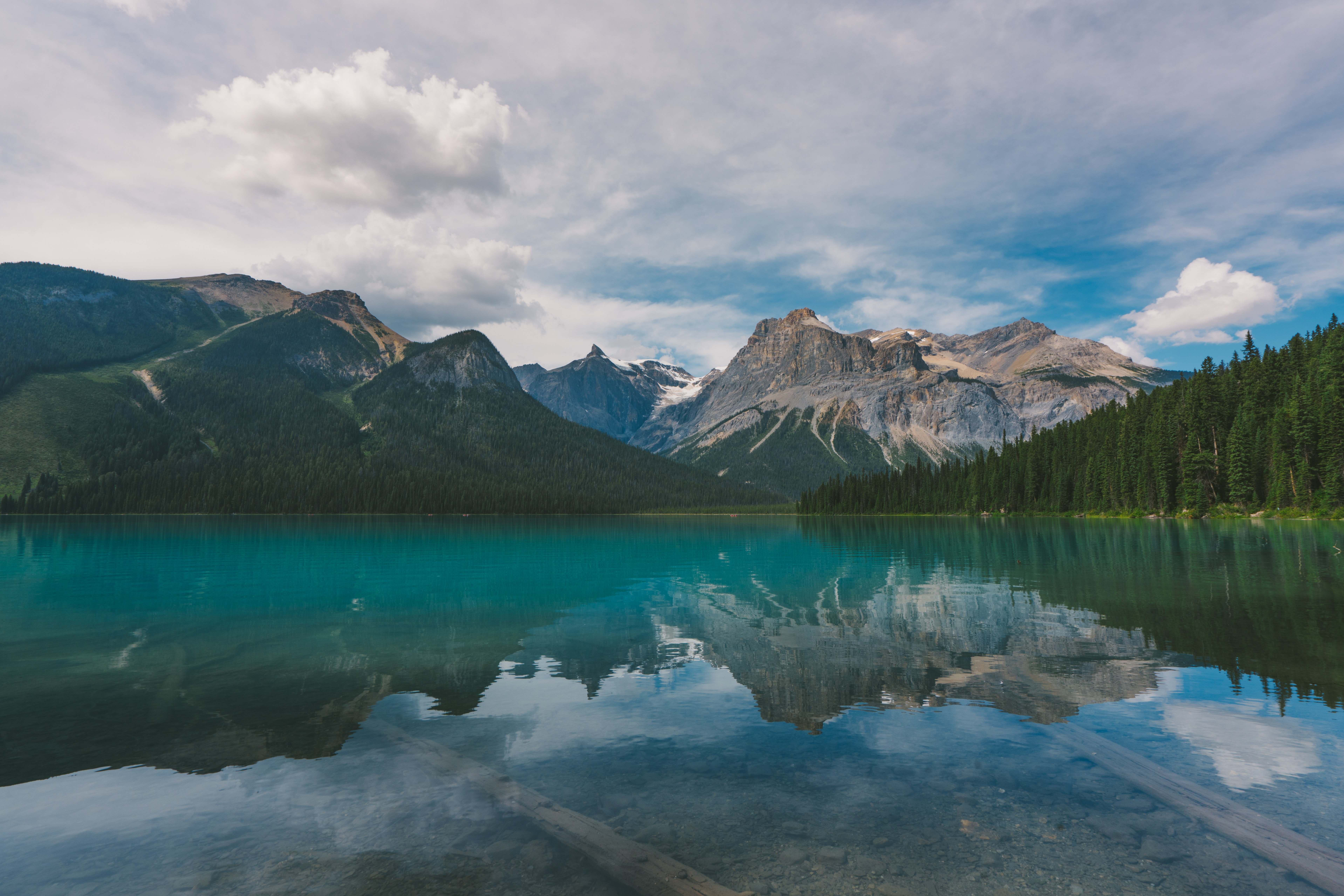 An emerald-green surface of a lake near granite mountains in Yoho National Park