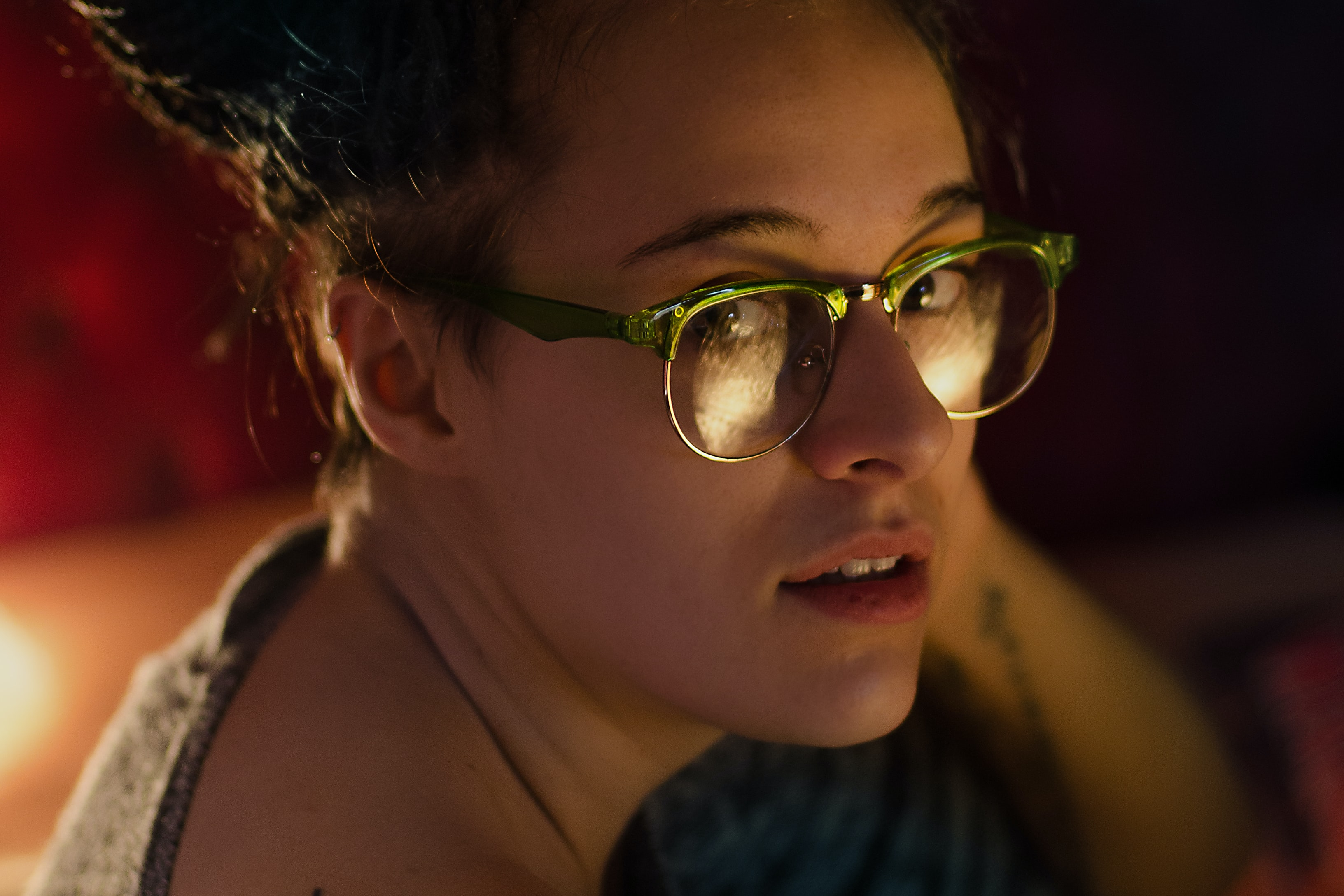 Close-up of a woman in glasses with a tattoo and hair up looking toward the camera