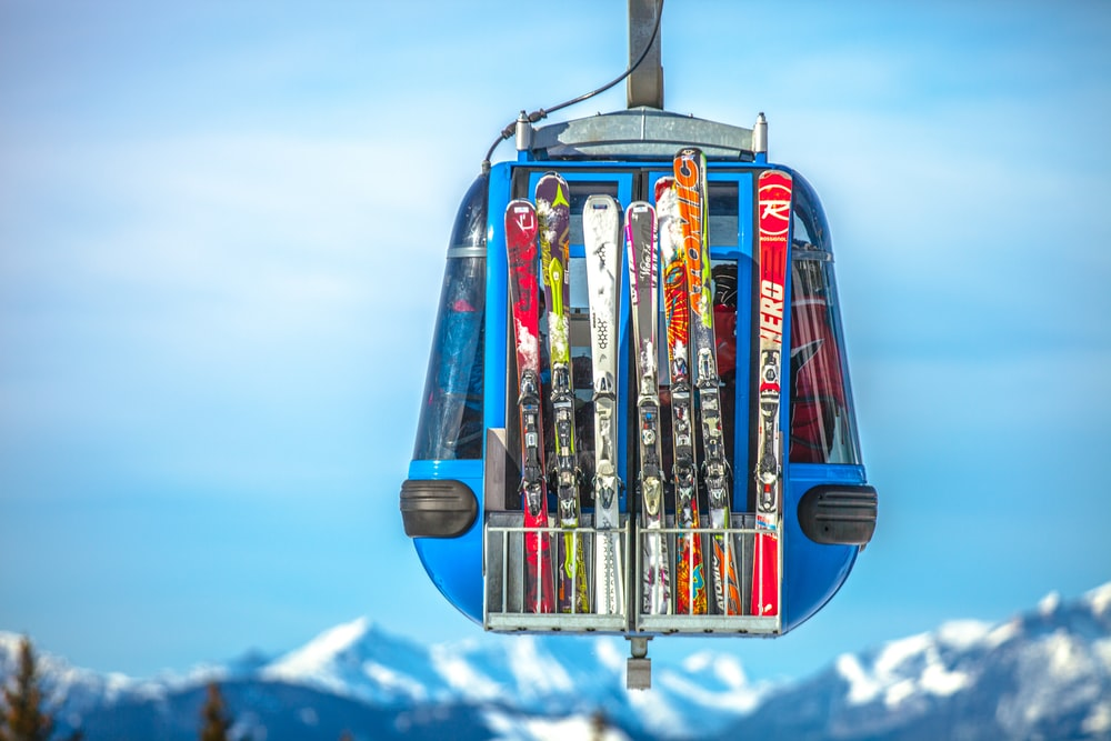 selective focus photography of ski blades on blue cable car