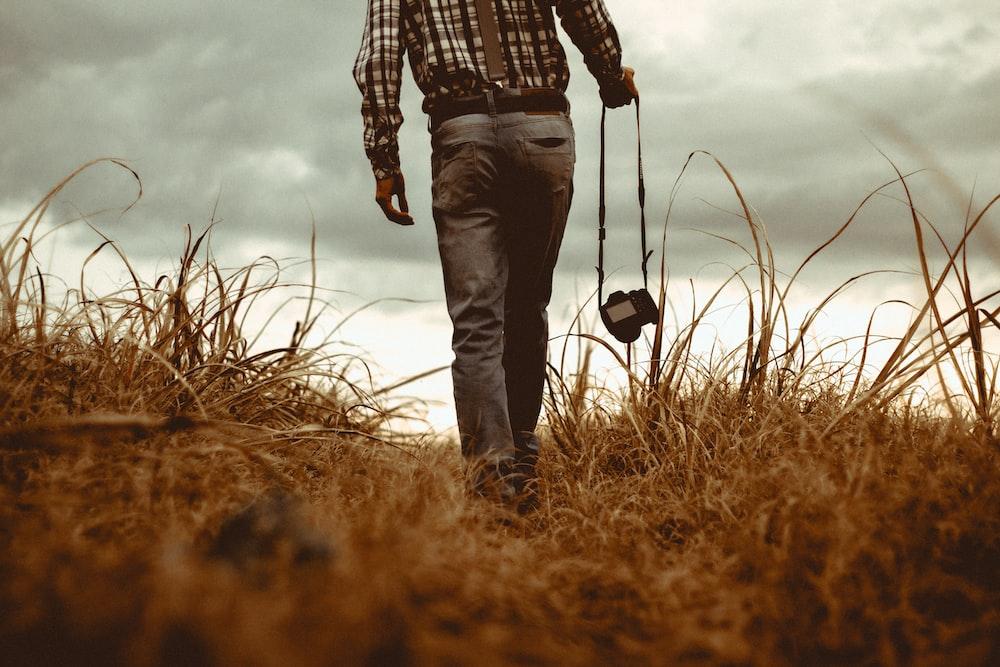 man holding DSLR camera walking through brown grass