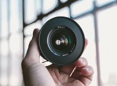 Guy holding a camera lense