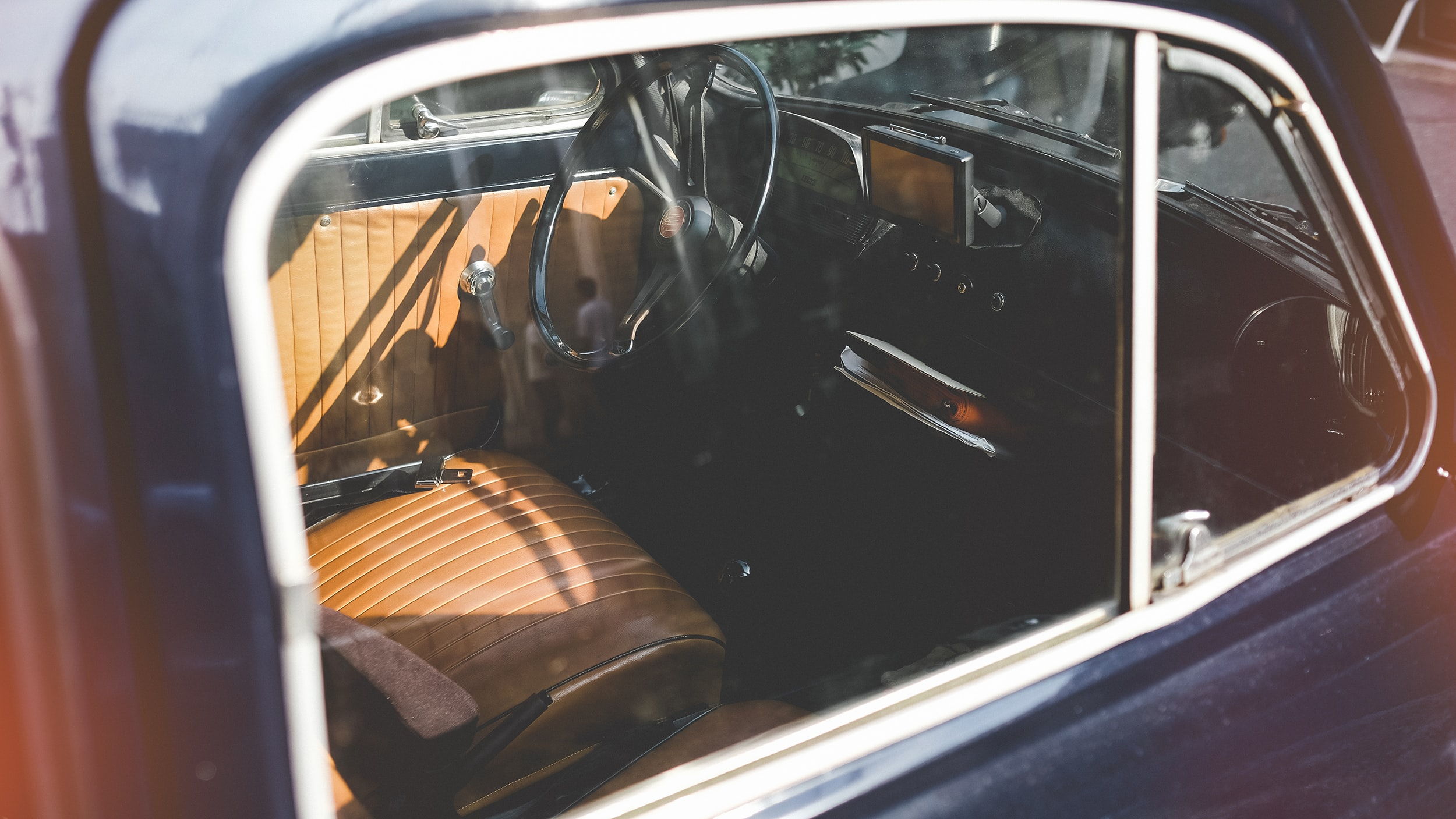 Interior of vintage car with brown leather seats from window