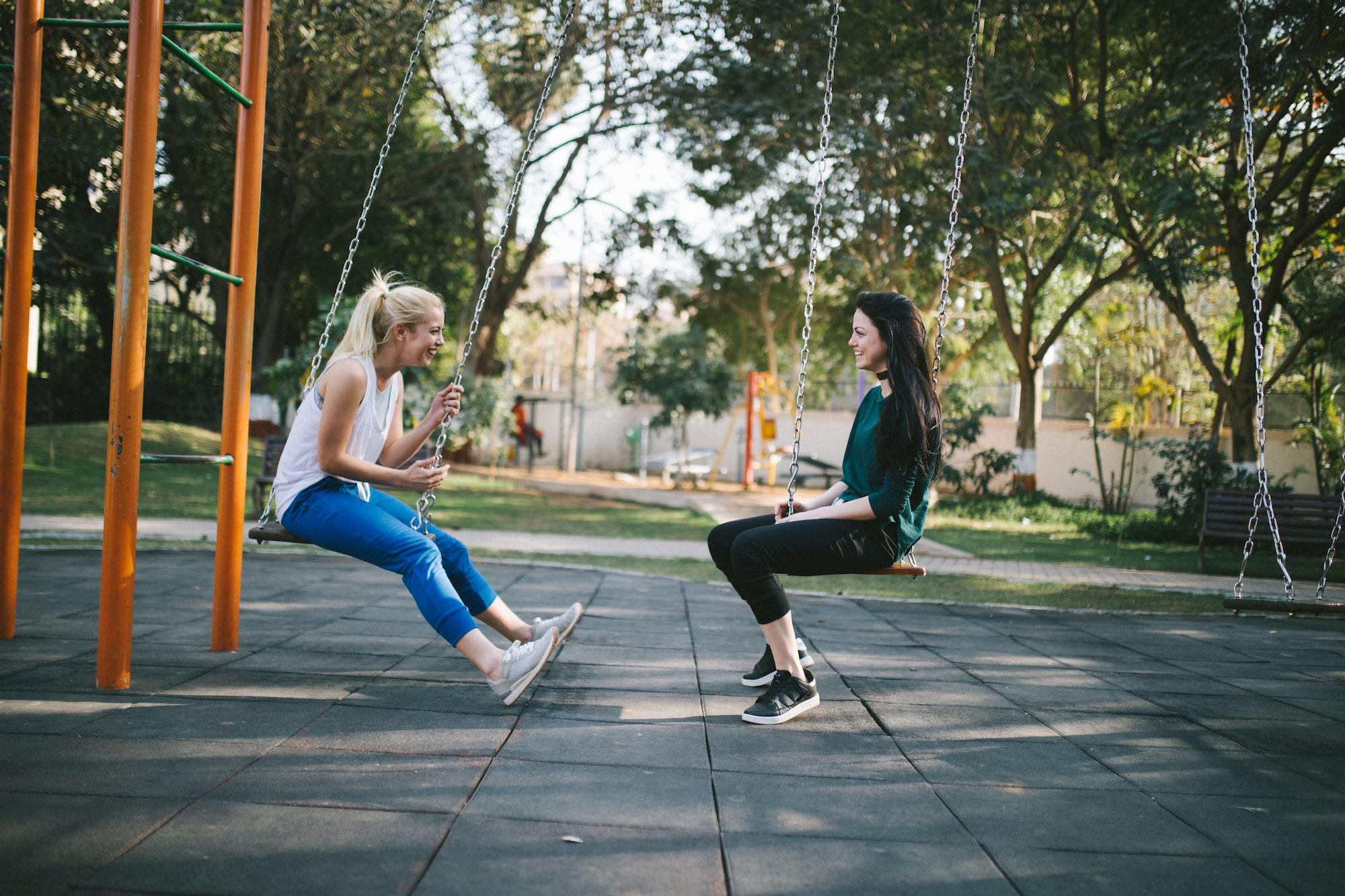 Friends talking on swing