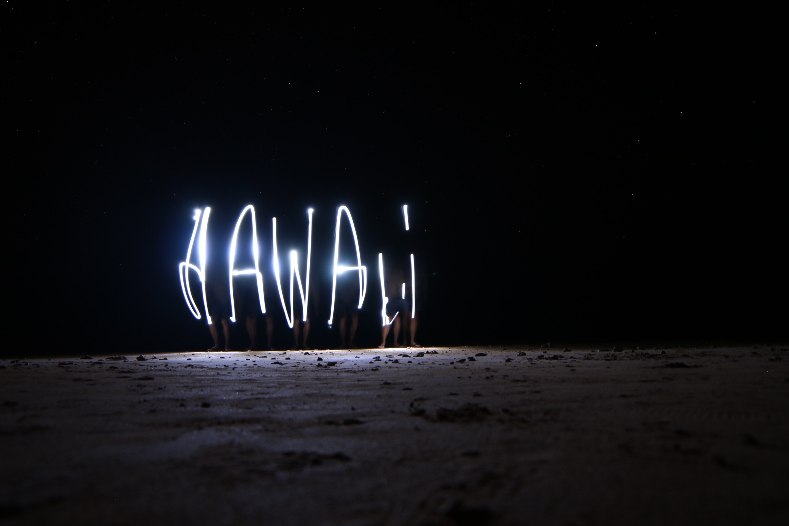 A night-time light painting that spells out HAWAII, taken on Anini Beach