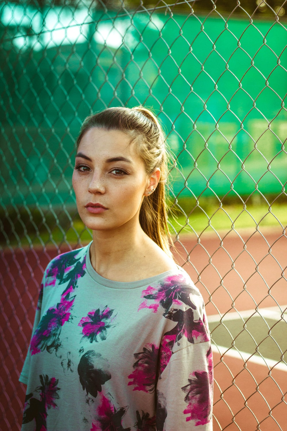 woman wearing floral top beside chain link fence during day