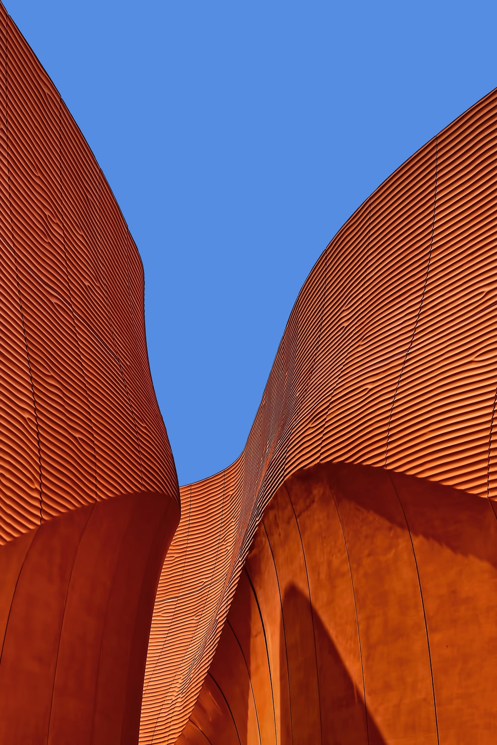 minimalist photography of brown wavy structure