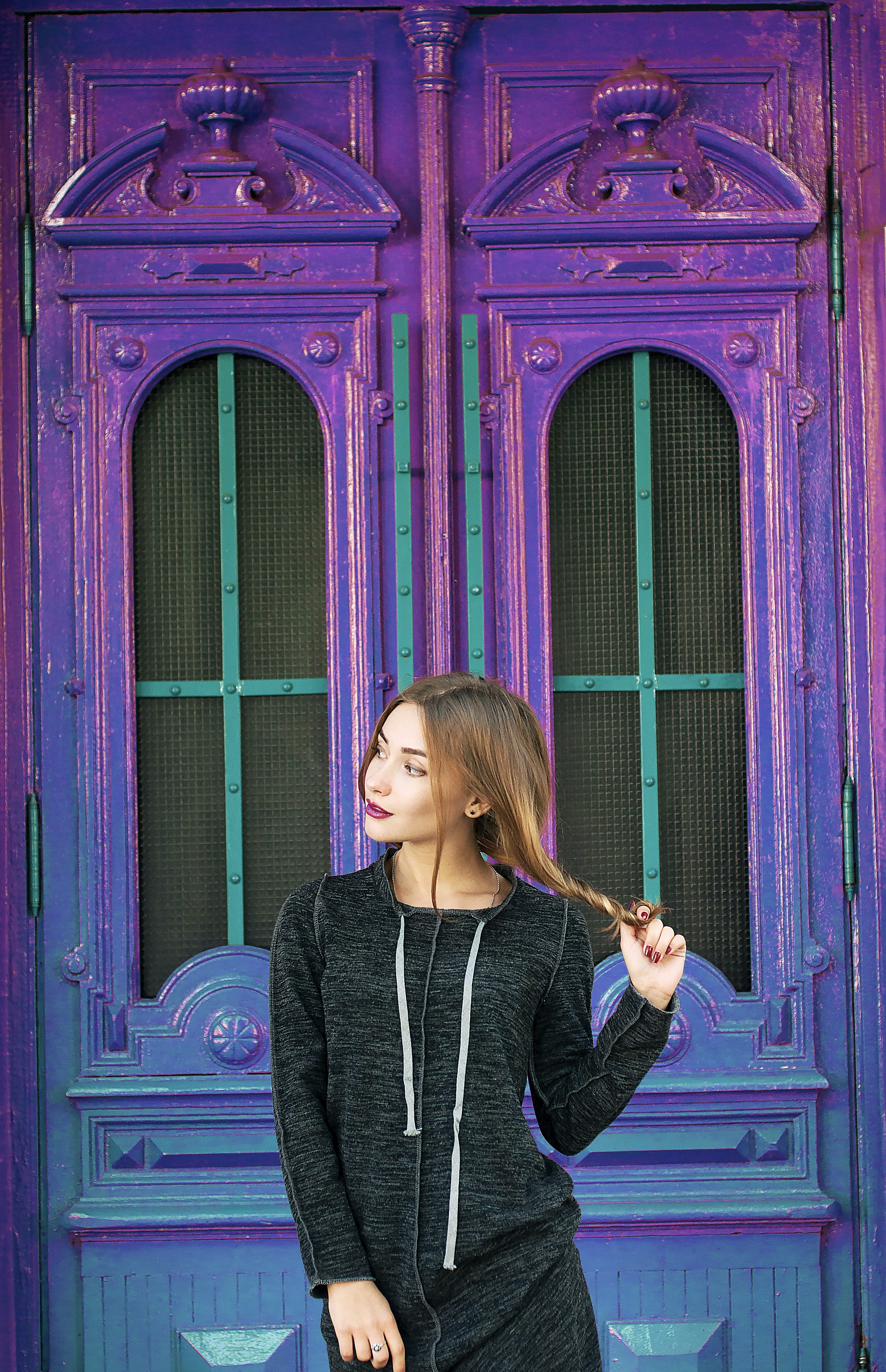 A woman holding her long hair while standing in front of a blue and purple building.