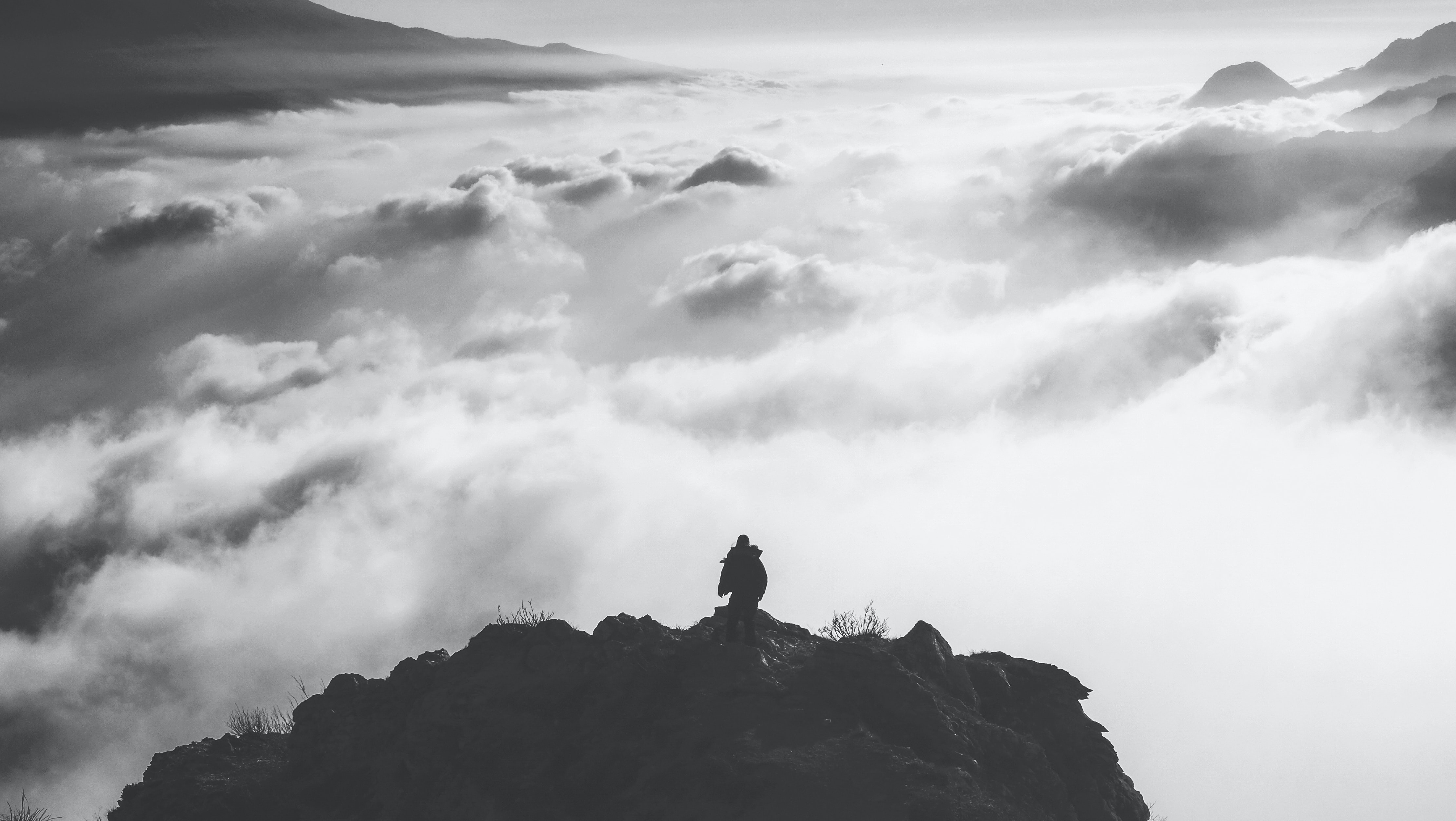 person standing at the edge of a mountain facing clouds during day