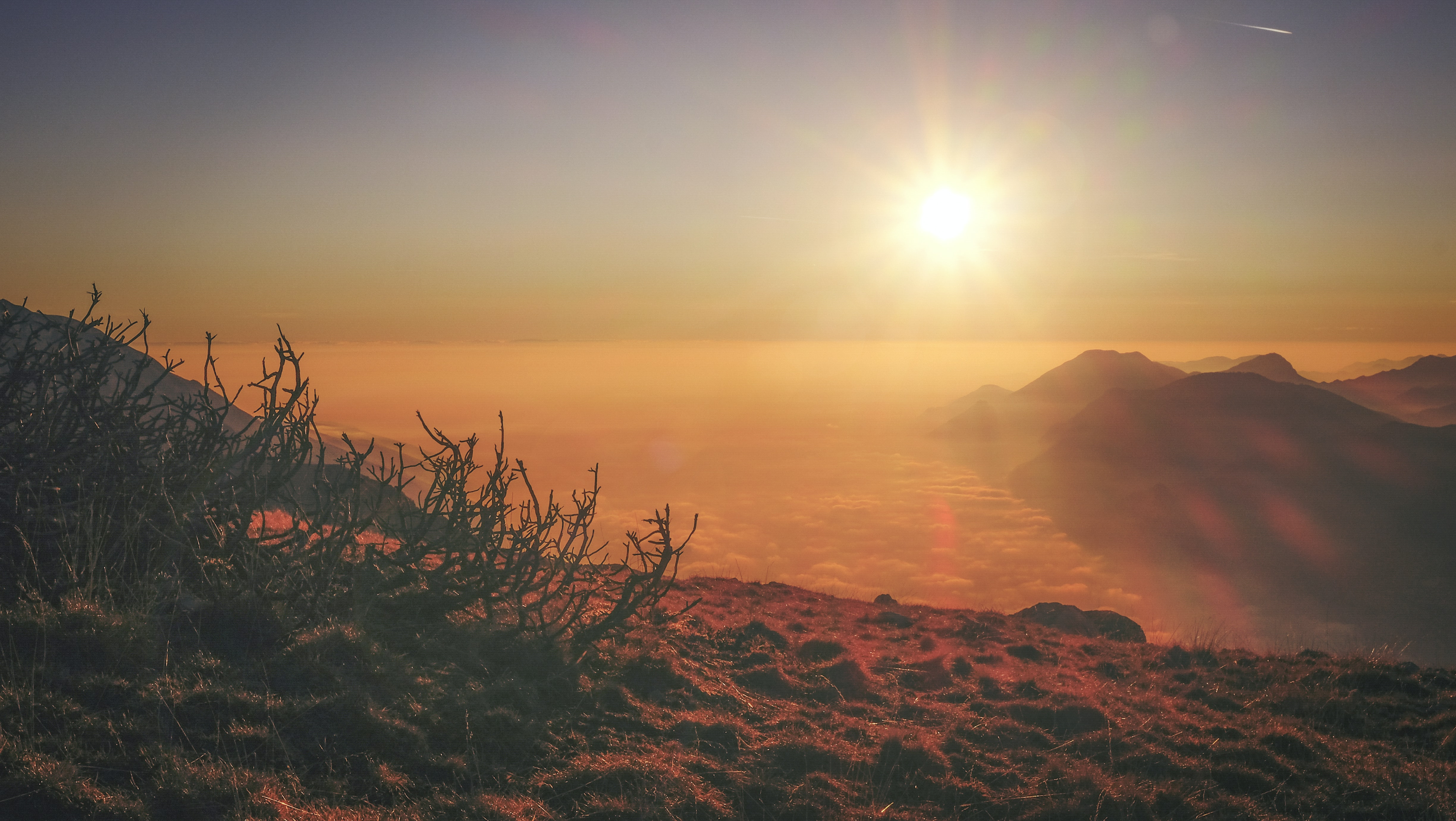 Sunrise shines on the desert fog and mountains in Monte Altissimo di Nago